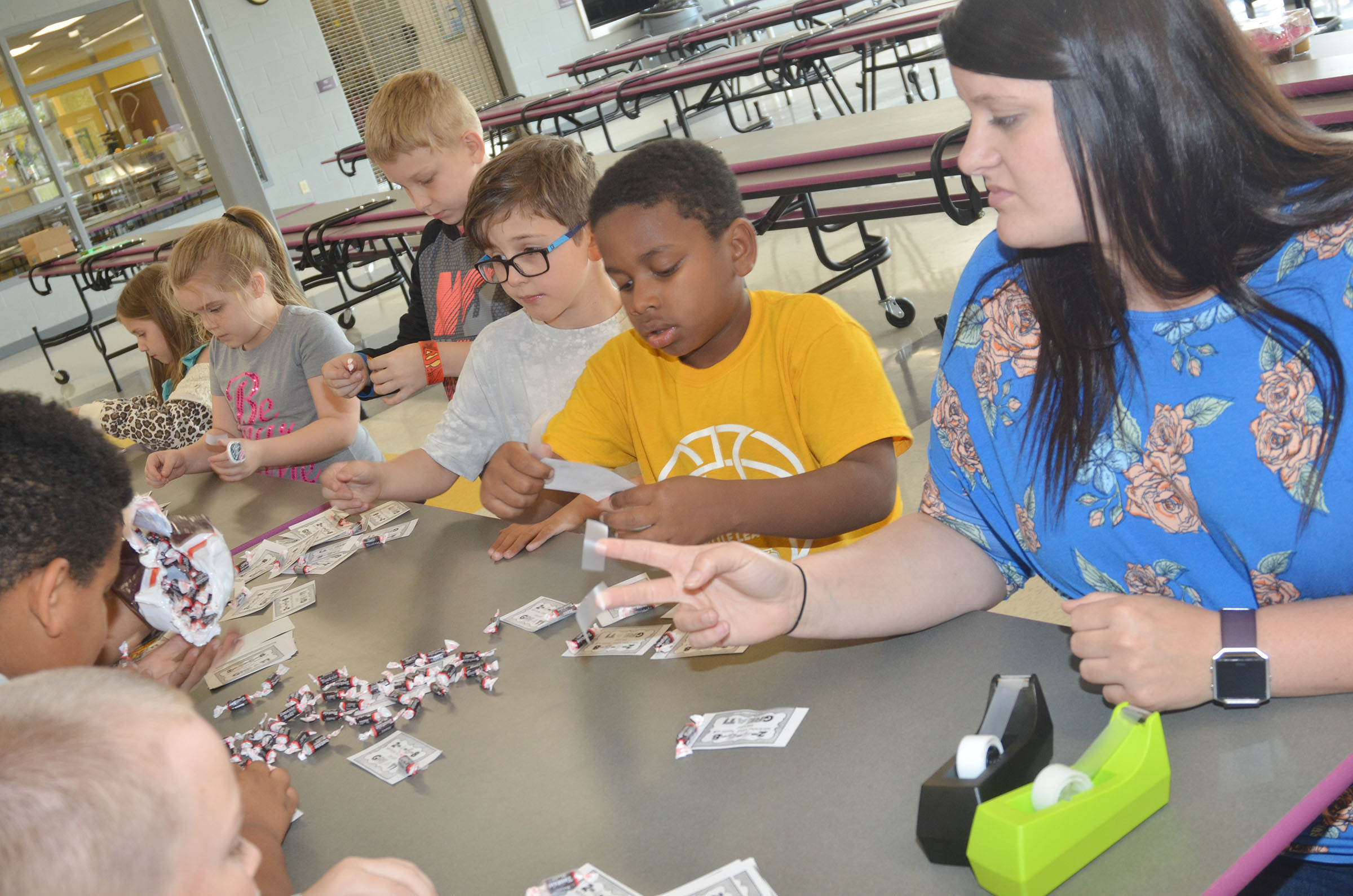 CES Explorers teacher Miriah Cox sorts Tootsie Rolls with second-graders to give to third-graders as a treat.