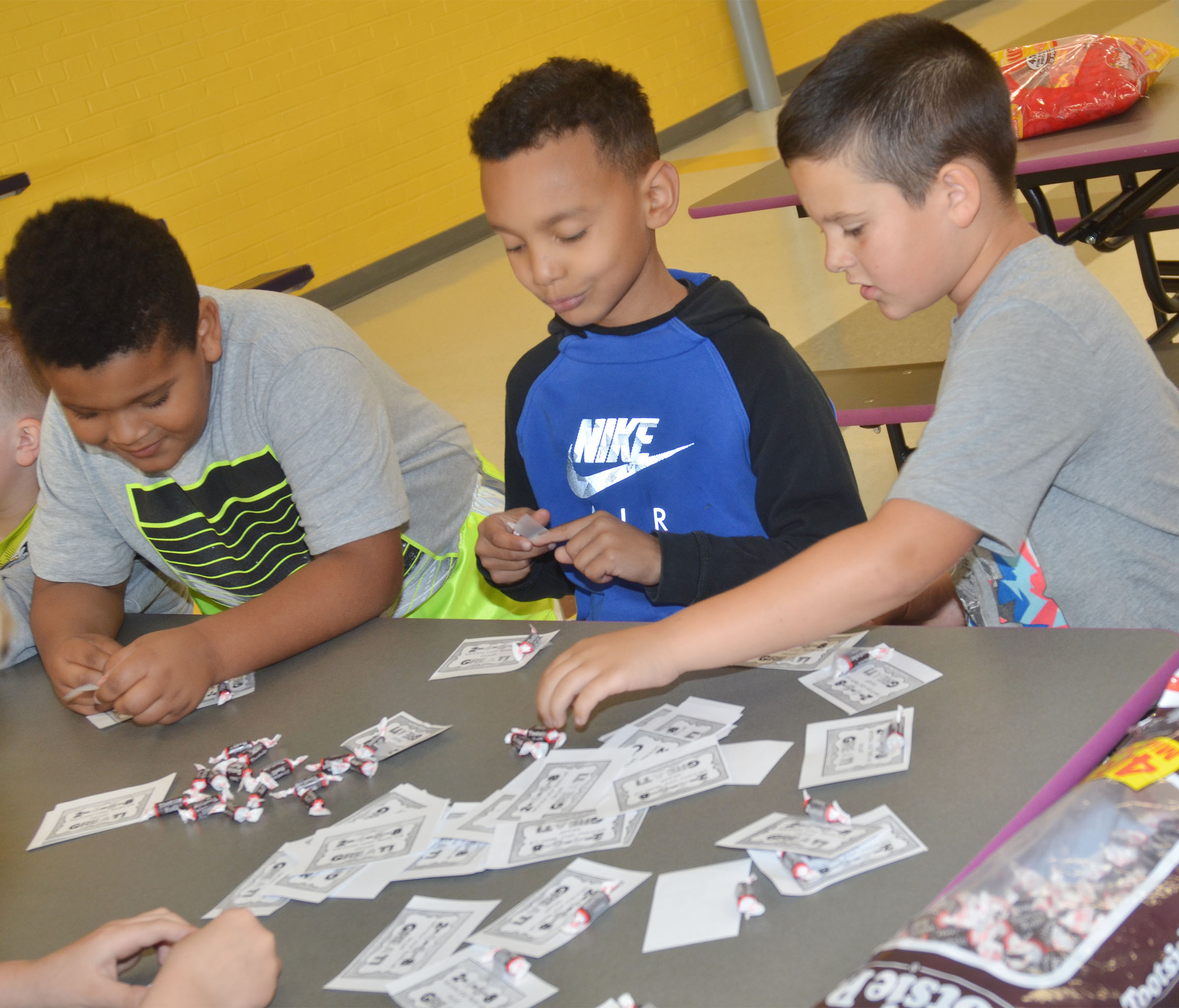 CES second-graders, from left, Jayden Moore, Maddox Hawkins and Damien Clark sort Tootsie Rolls for third-graders.