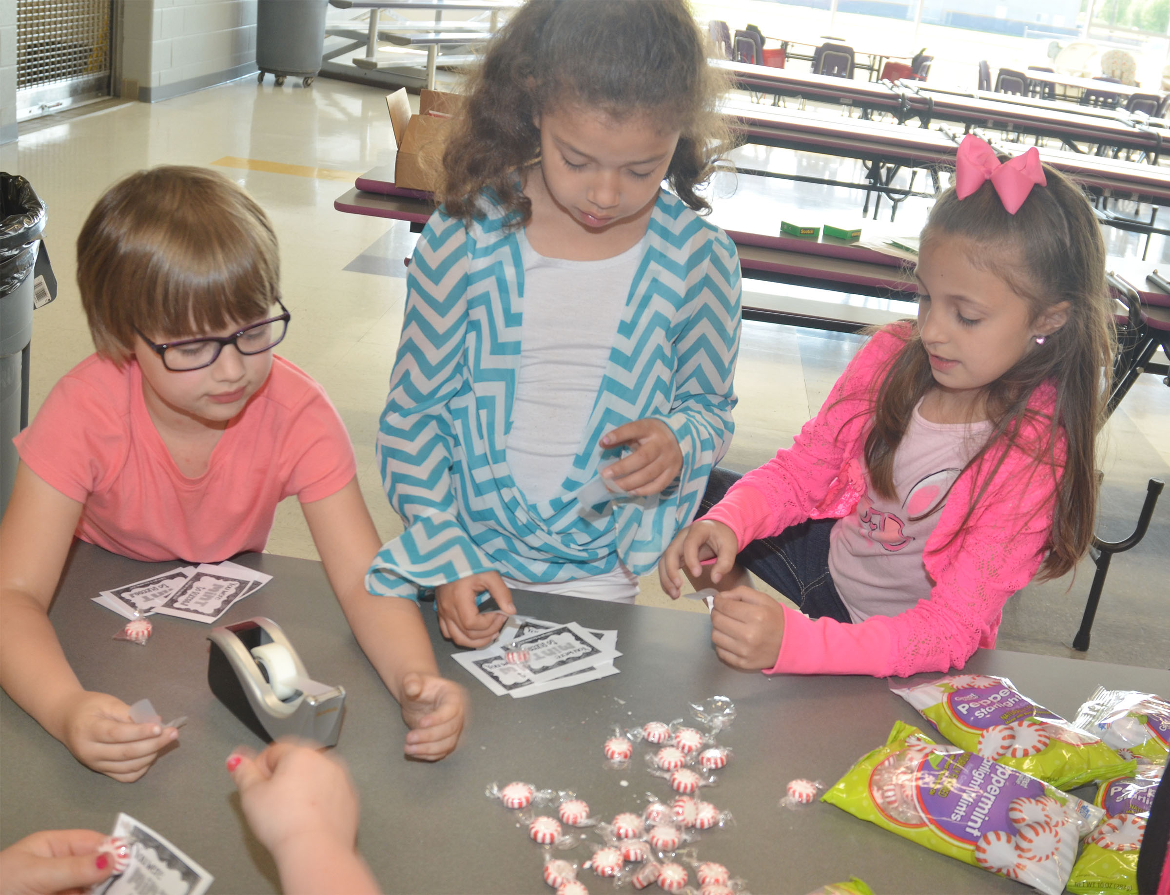 From left, CES first-graders Addelyn Dooley, Ammarissa Nunez and Lillian Martin sort peppermints for third-graders.