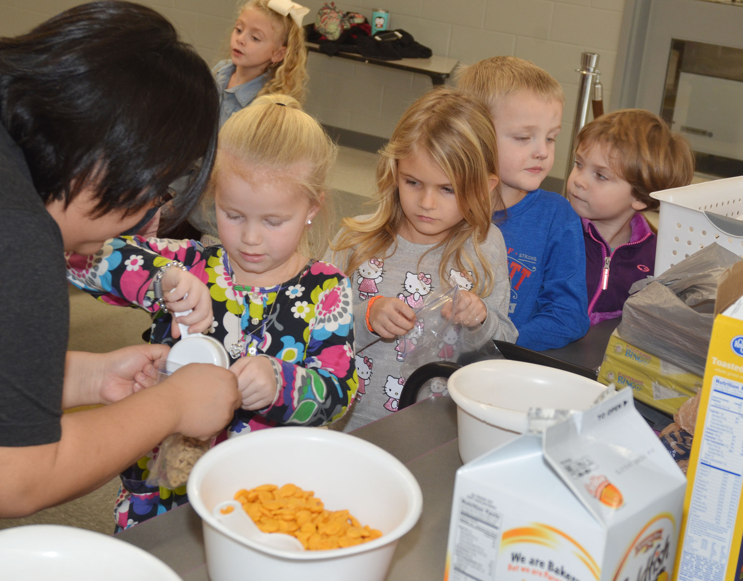 CES instructional assistant Brittany Johnson helps kindergartener Lillie Judd make her trail mix, as Judd's classmates wait their turn.