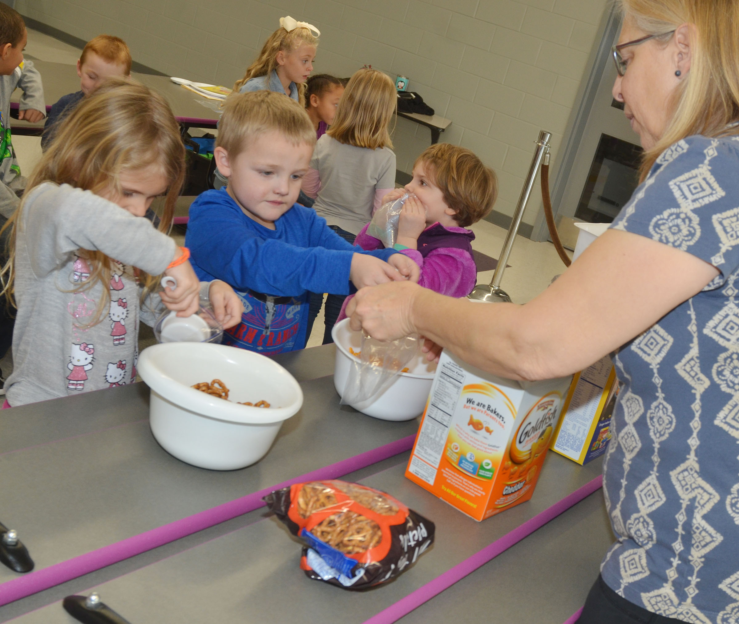 Angie Freeman, expanded foods and nutrition program assistant at Taylor County Extension Office, helps CES kindergartener Tristian Harris make his trail mix, as Gracie Gebler adds pretzels to hers.
