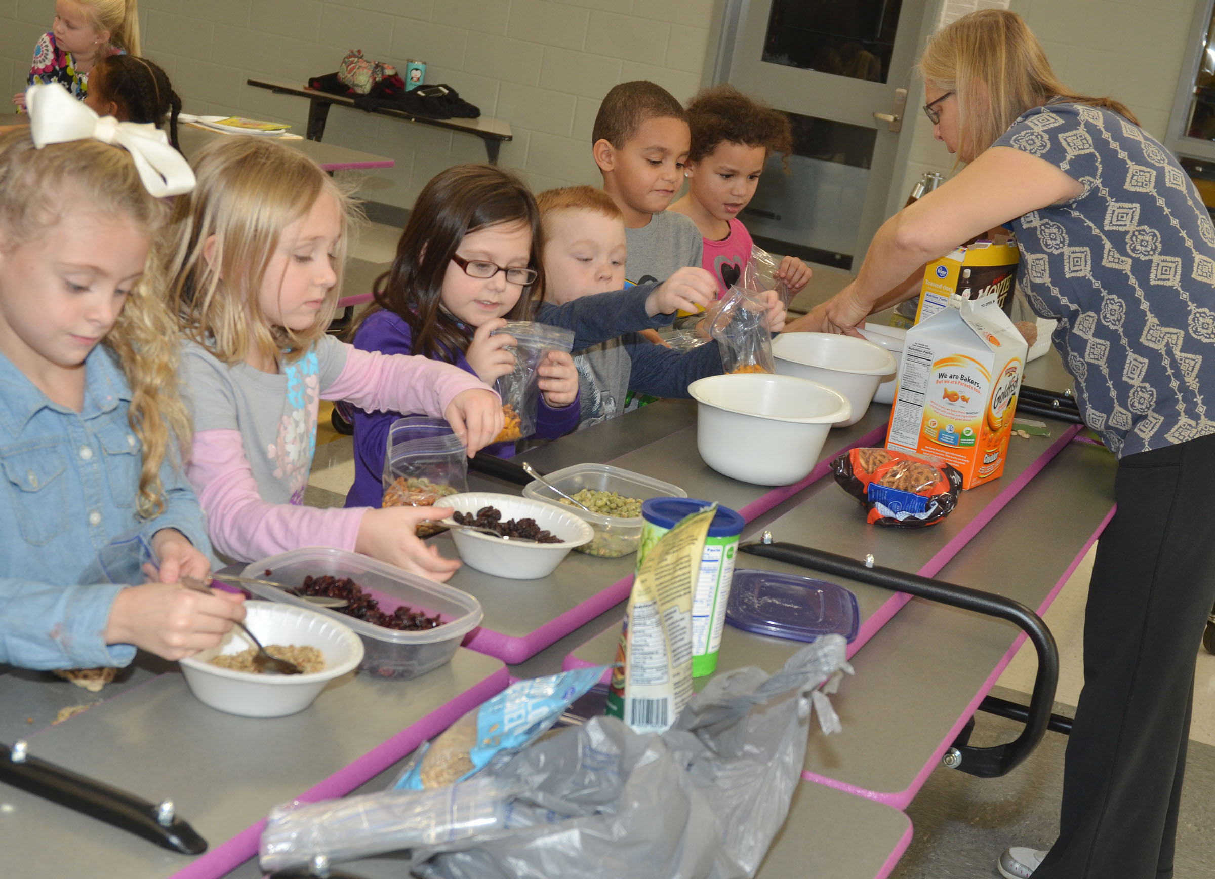 Angie Freeman, expanded foods and nutrition program assistant at Taylor County Extension Office, helps CES kindergarteners make trail mix. From left are Aliyah Litsey, LeeAnna Garvin, Trinity Clark, Daven Davis, Quincy Travis and Aleeya Spaulding.