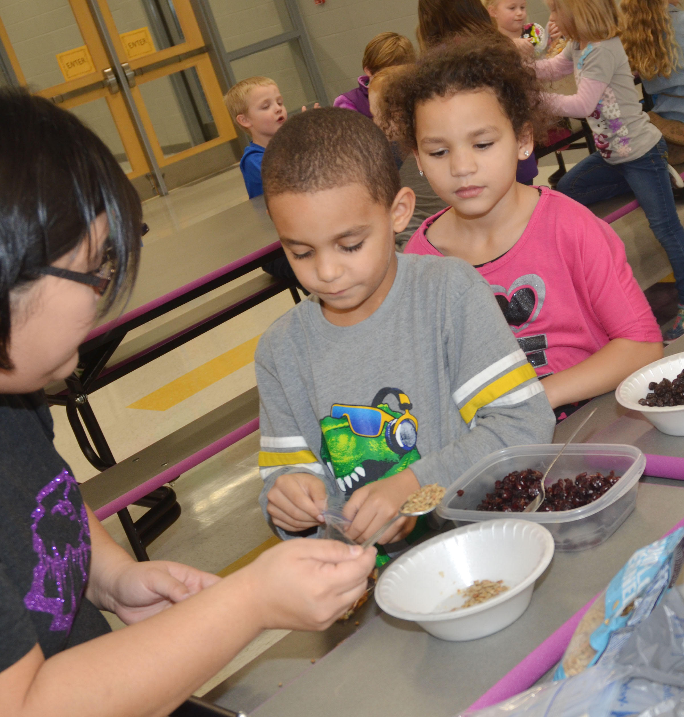 CES instructional assistant Brittany Johnson helps kindergartener Quincy Travis make his trail mix, as classmate Aleeya Spaulding waits her turn.