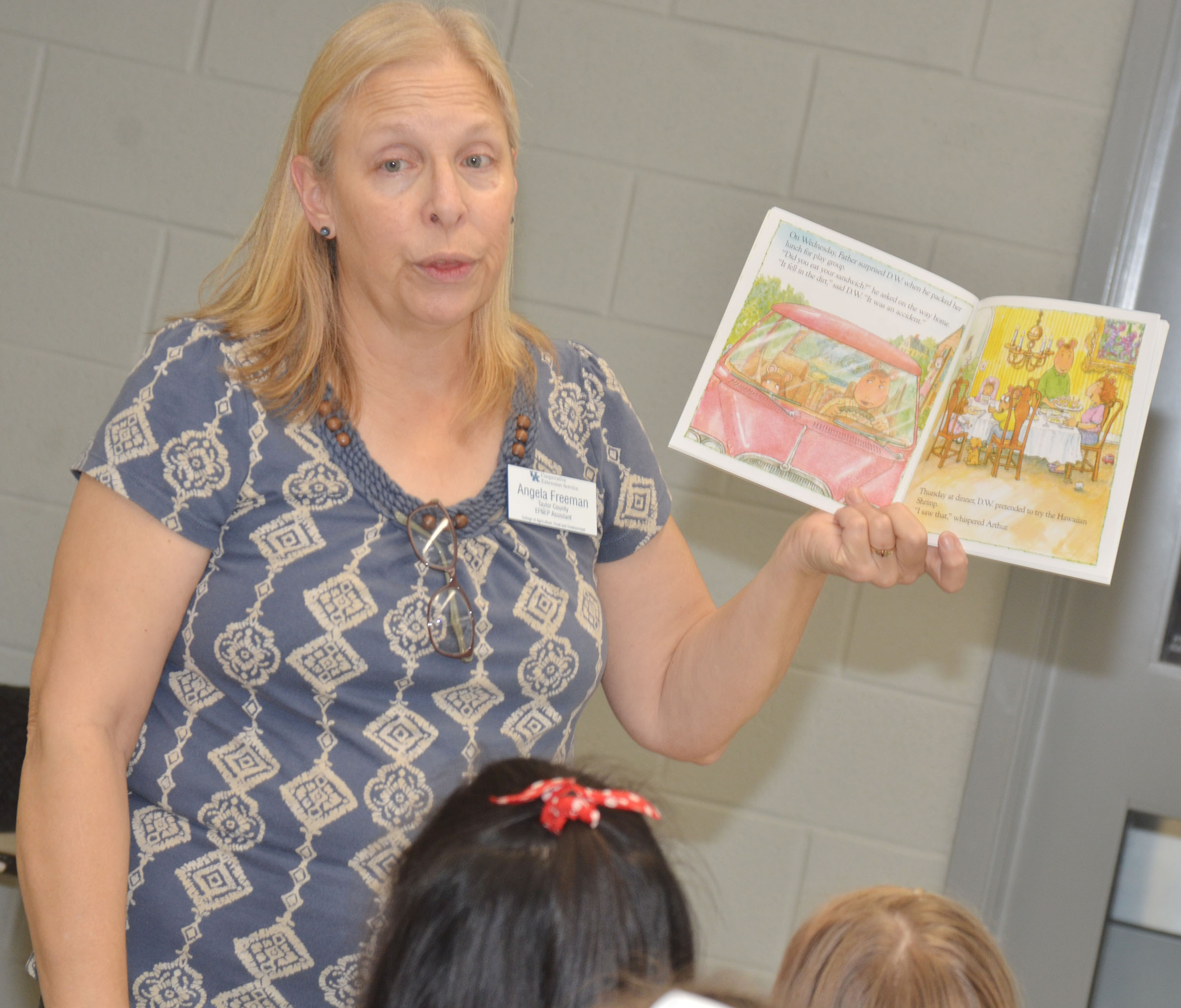 Angie Freeman, expanded foods and nutrition program assistant at Taylor County Extension Office, reads to CES students about a girl who didn't like vegetables but learned she did after she tried them.