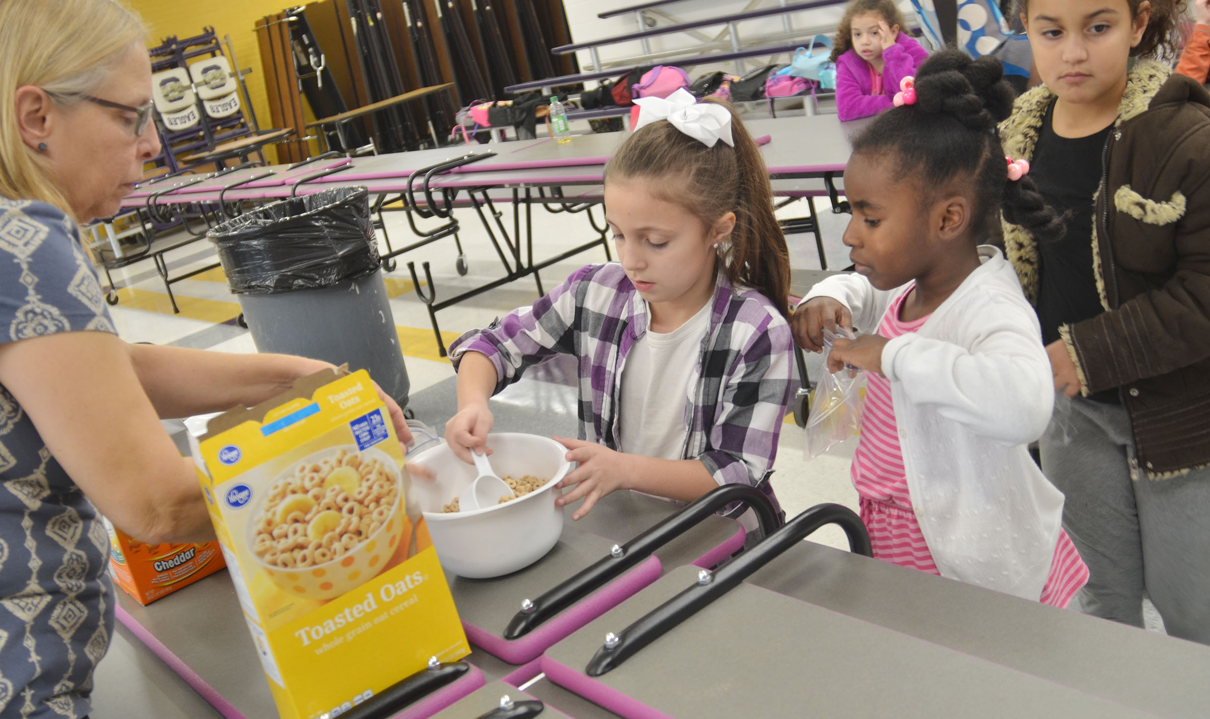 Angie Freeman, expanded foods and nutrition program assistant at Taylor County Extension Office, helps CES first-graders Lillian Martin, at left, and Destini Gholston make their trail mix.