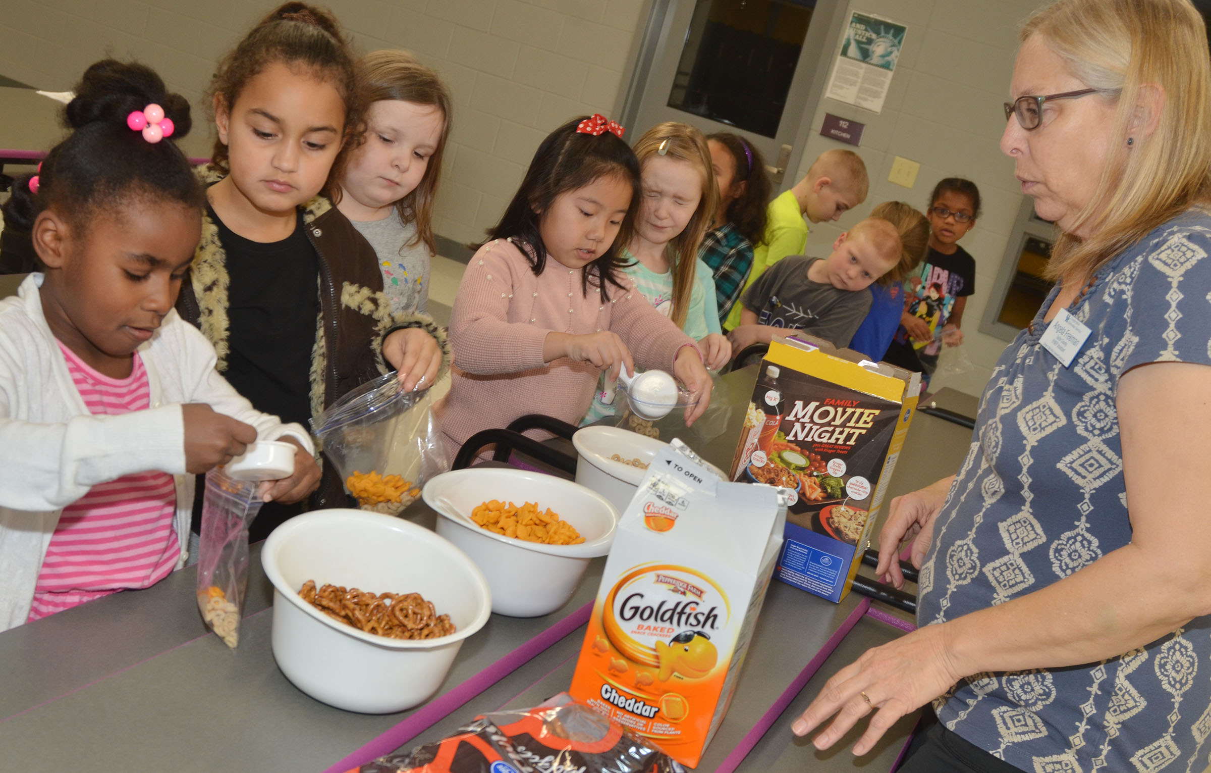 Angie Freeman, expanded foods and nutrition program assistant at Taylor County Extension Office, helps CES first-graders make their trail mix. From left, Destini Gholston, Maleigha Travis, Kierra Maupin and Tina Jiang add snacks to their bags.