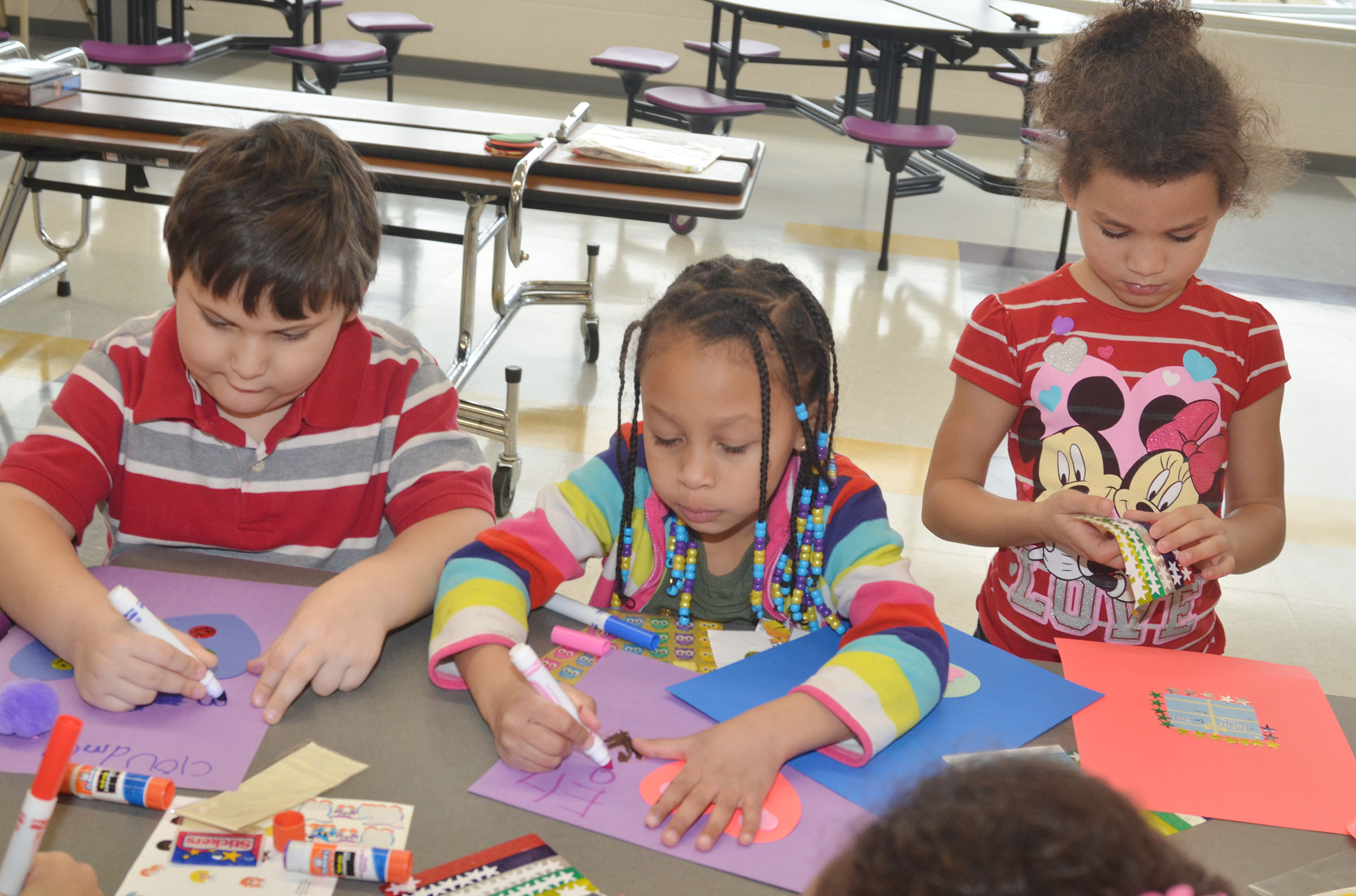 From left, CES kindergarteners Cloud Malone, Elyzabeth Fisher and Aleeya Spaulding make Valentine cards.