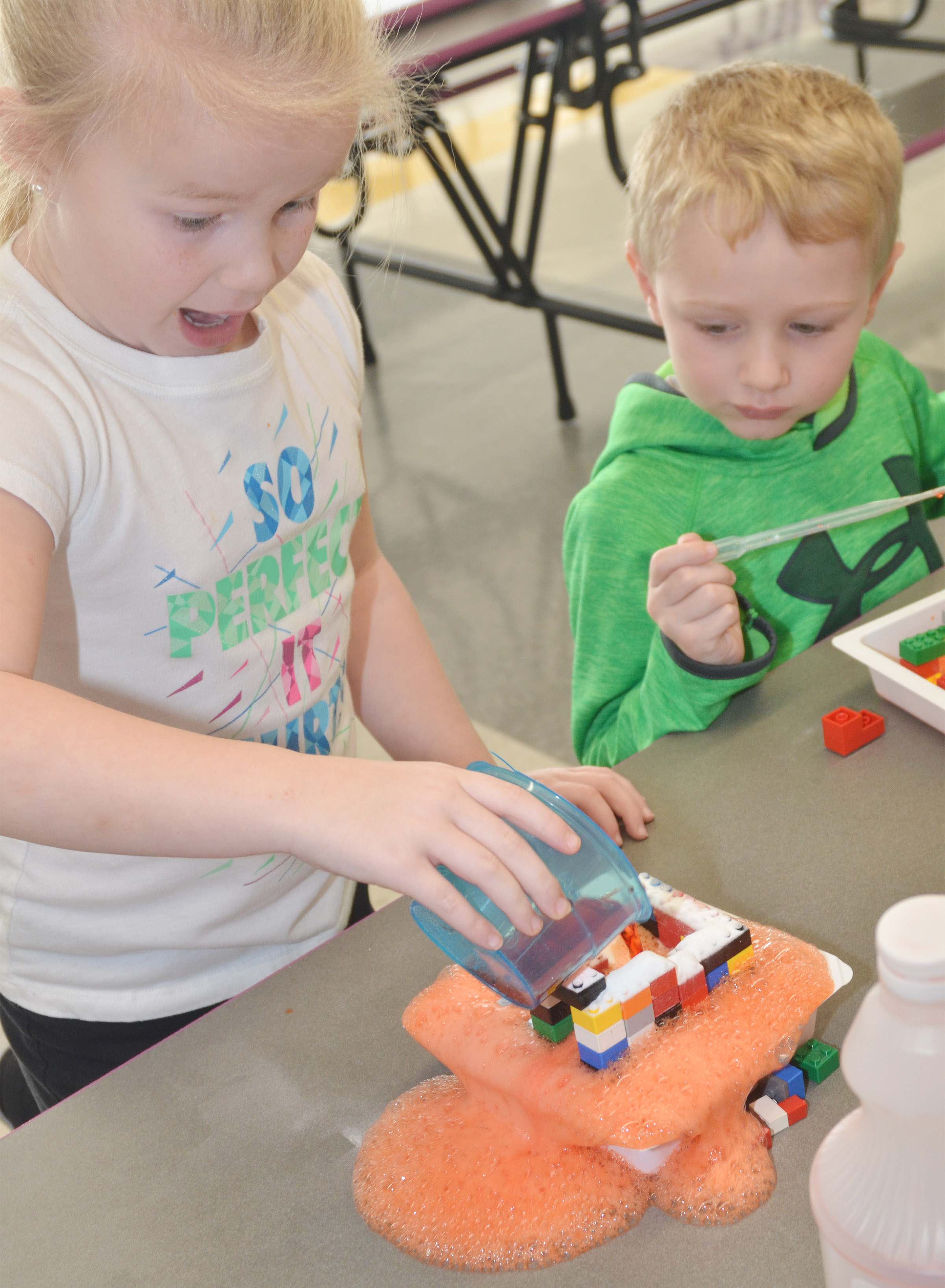 CES kindergartener Lillie Judd reacts as she pours vinegar on her Lego volcano, as classmate Jackson Wright watches.