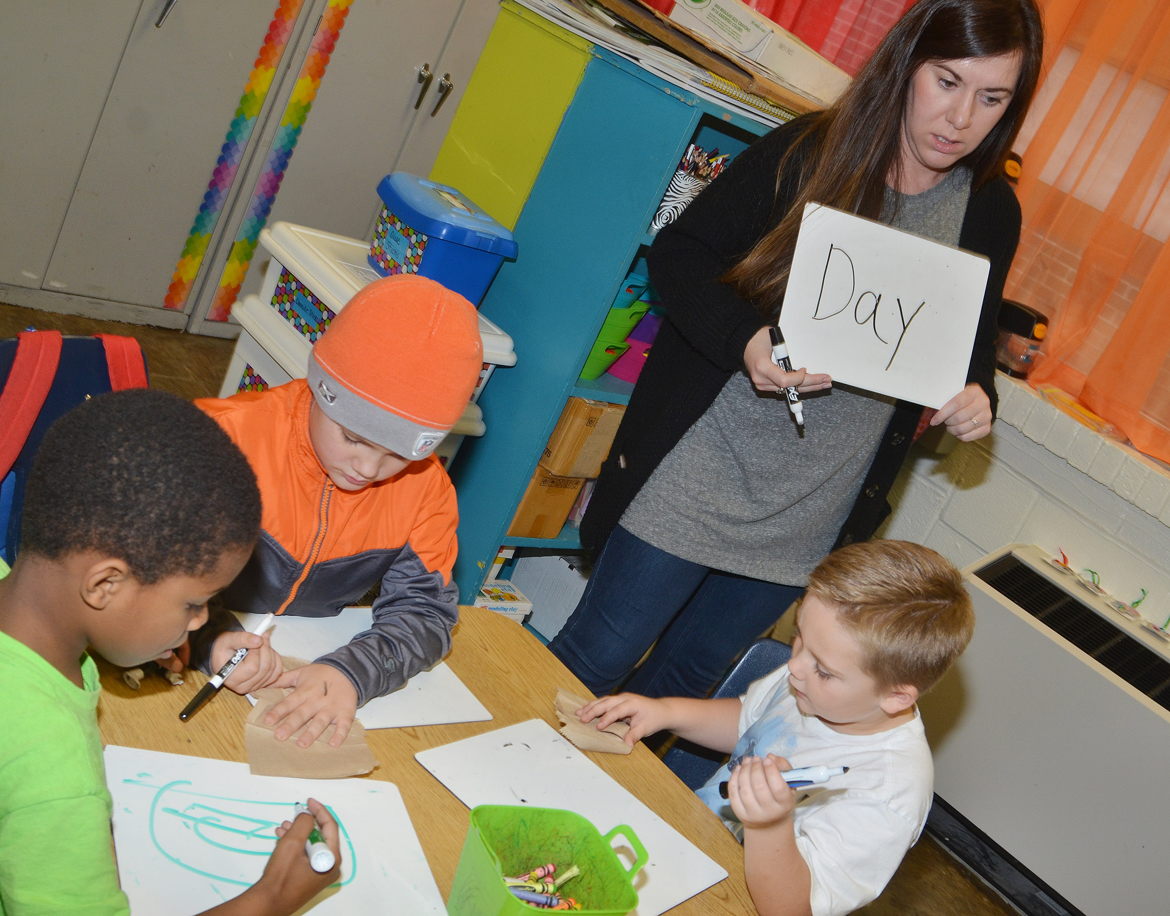 CES Wings Express teacher Courtney Mills helps kindergarten students, from left, Kaiyden Vancleave, Dawson Morton and Jacob Sandidge write letters.