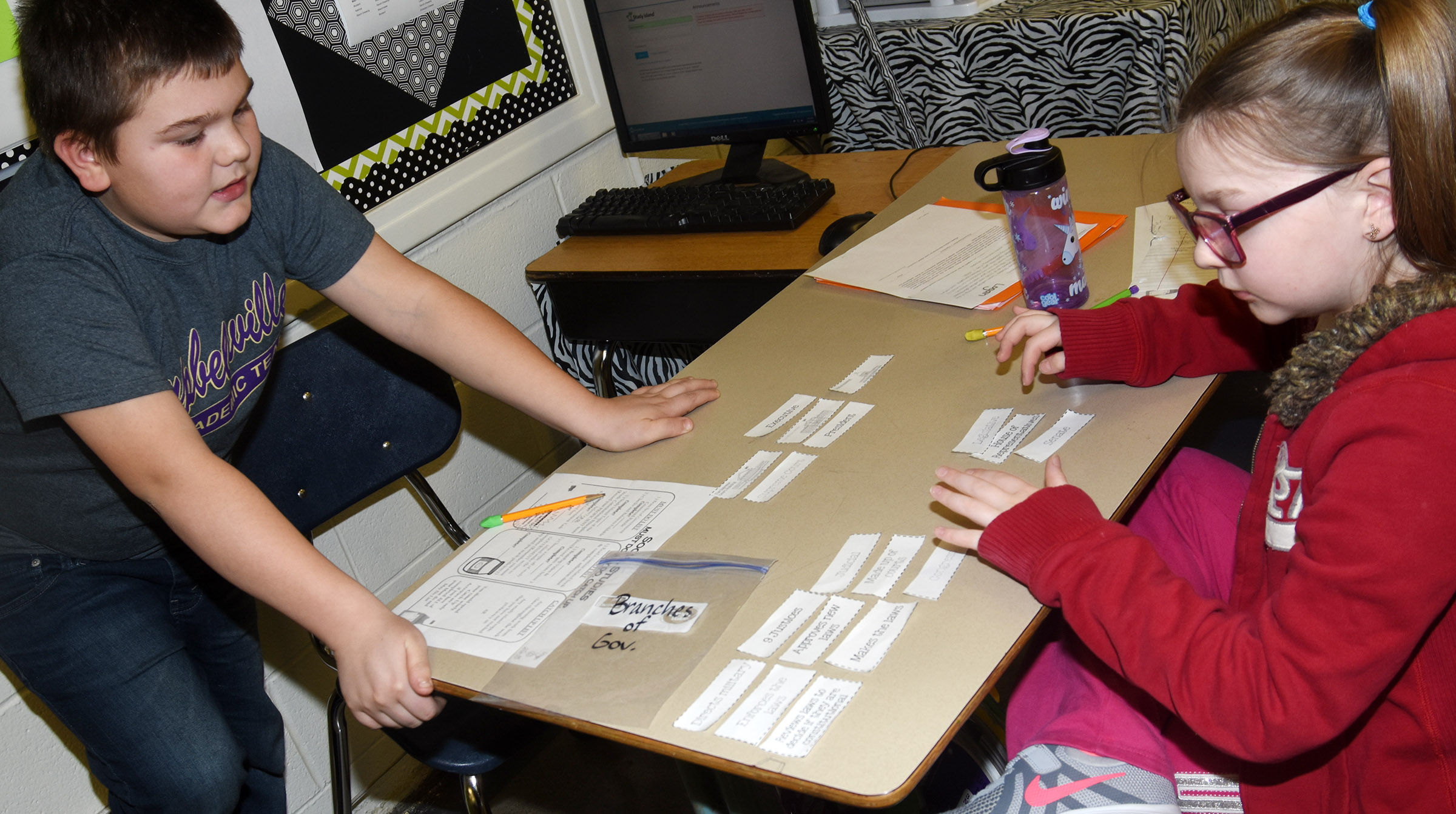 CES fifth-graders Logan England, at left, and Morgan Spears work together to play a branches of government card sort game.