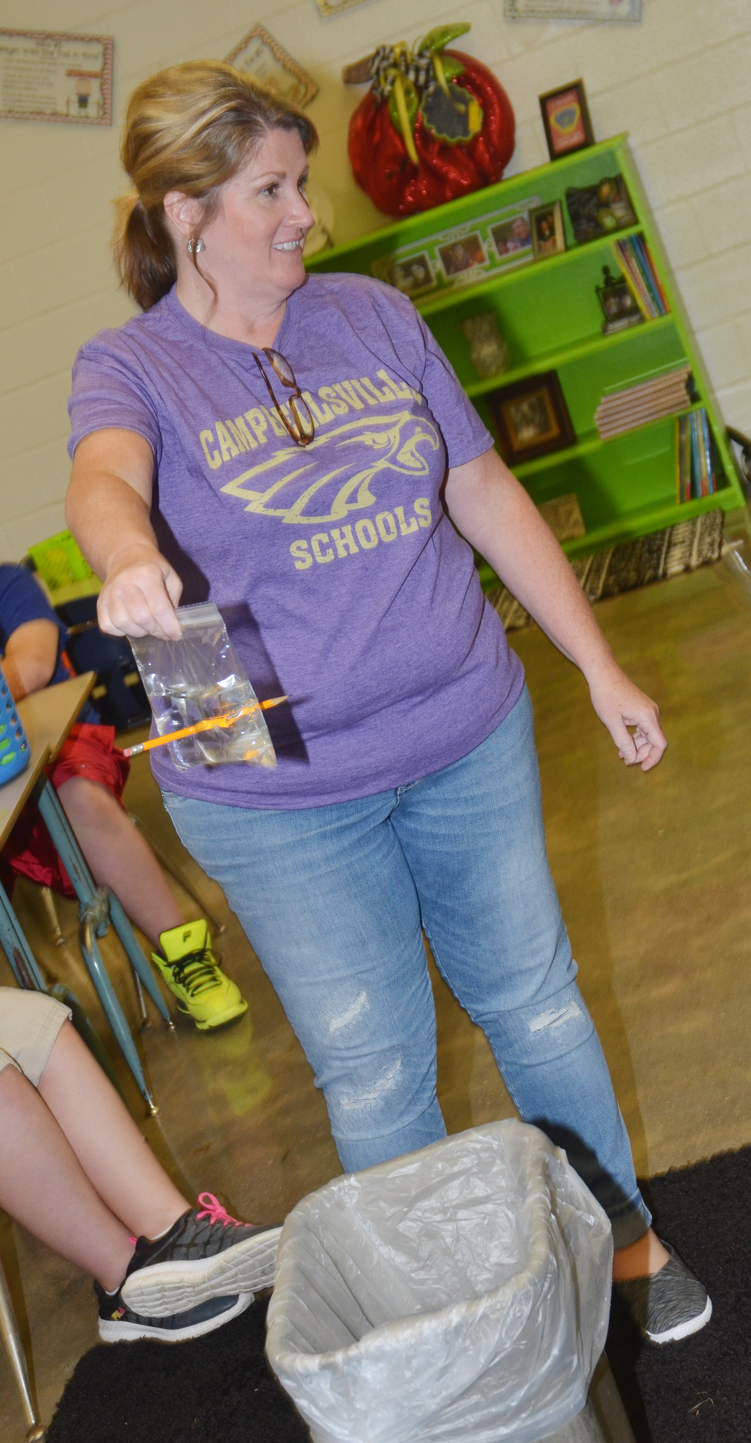 CES fifth-grade teacher Donna White demonstrates how a Ziploc bag acts as a polymer, and, therefore, water inside doesn't spill when a pencil pierces the bag.