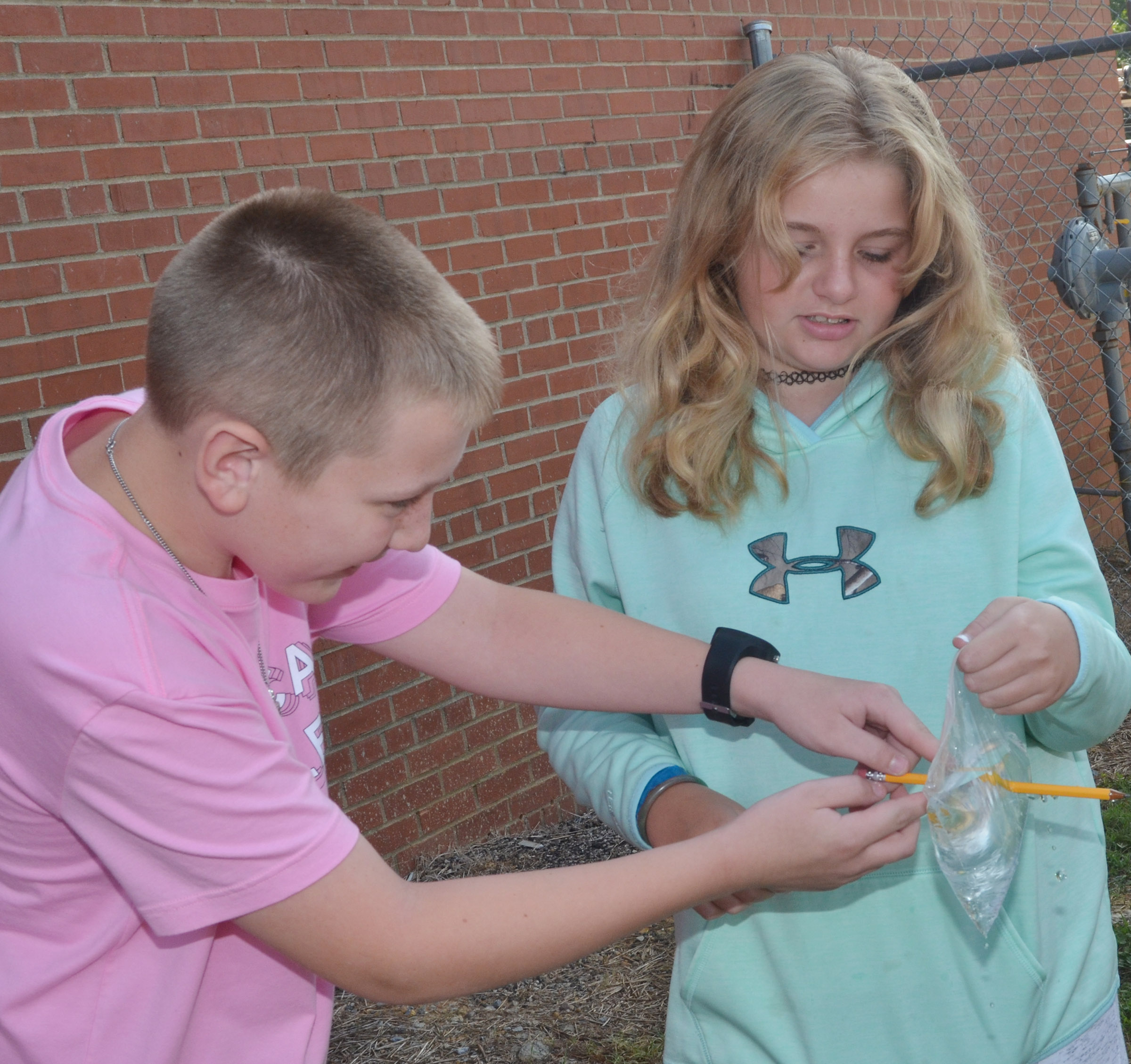CES fifth-graders Kaleb Miller, at left, and Dakota Broyles see how a Ziploc bag acts as a polymer, and, therefore, water inside doesn't spill when a pencil pierces the bag.