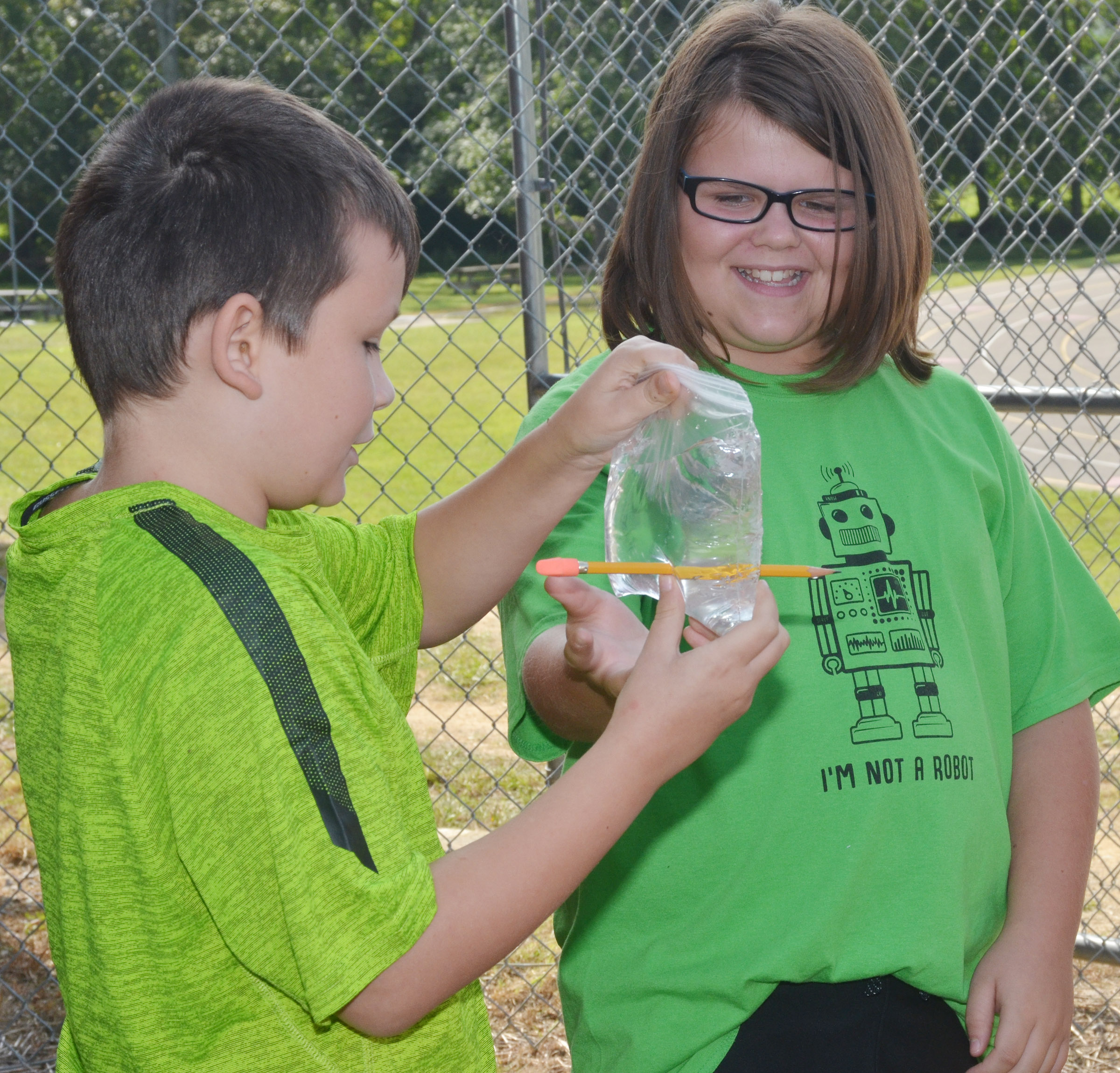 CES fifth-graders Mason Fisher, at left, and Keeley Dicken see how a Ziploc bag acts as a polymer, and, therefore, water inside doesn't spill when a pencil pierces the bag.