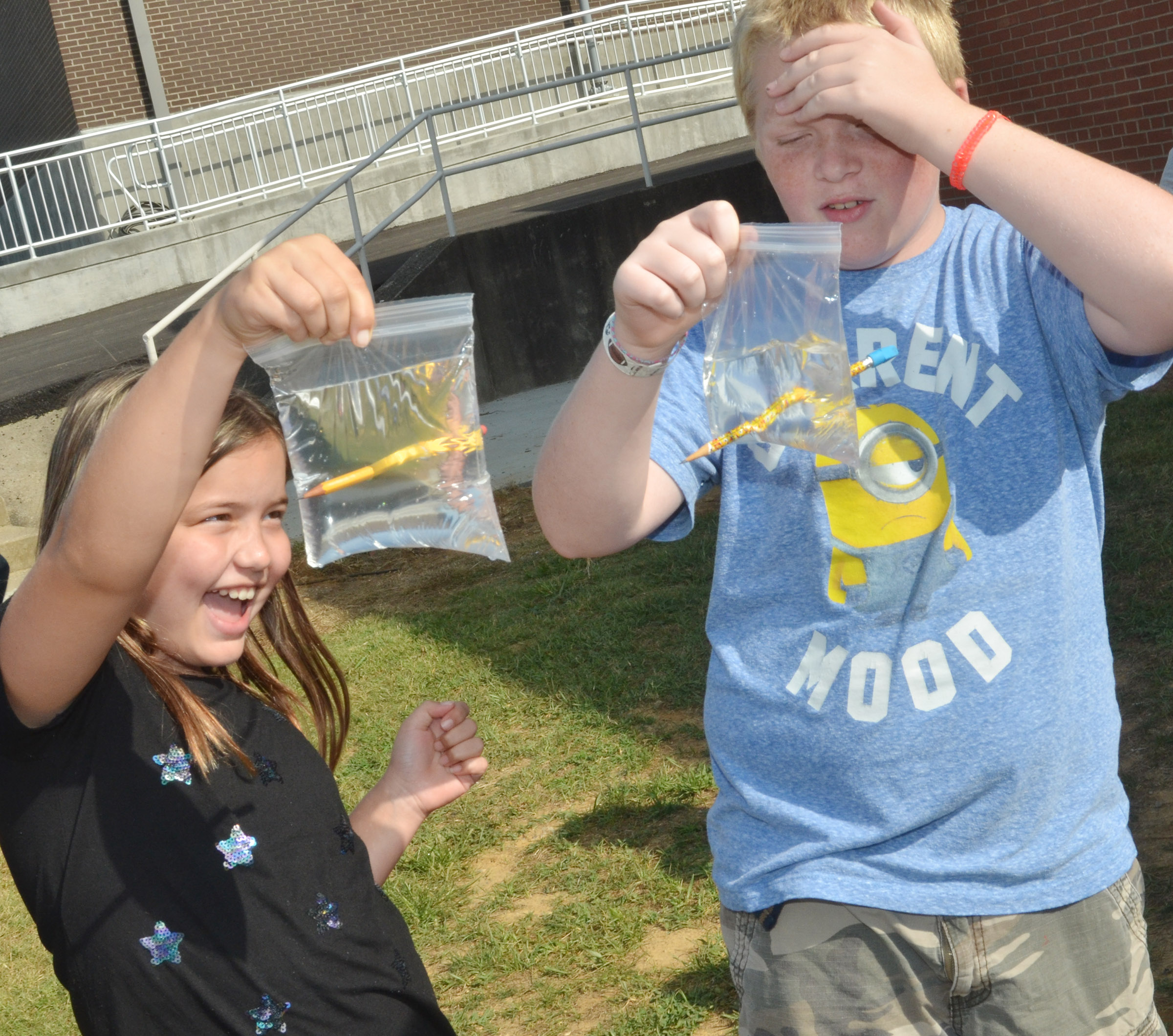 CES fifth-graders Kate Billeter, at left, and Simon Wilkerson see how a Ziploc bag acts as a polymer, and, therefore, water inside doesn't spill when a pencil pierces the bag.