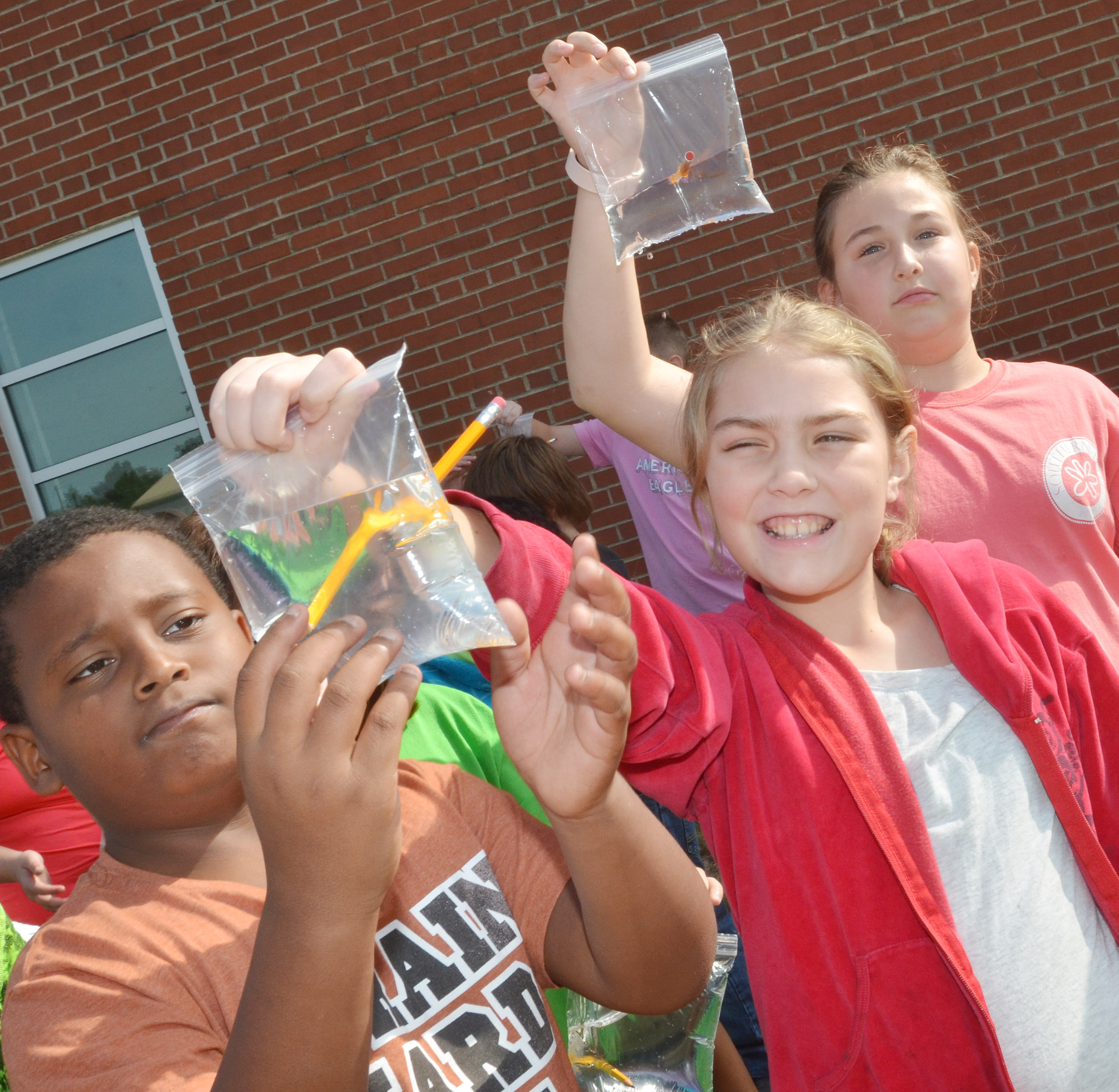 CES fifth-graders, from left, KeKe Miller, Harley Couch-Allen and Riley Newton see how a Ziploc bag acts as a polymer, and, therefore, water inside doesn't spill when a pencil pierces the bag.