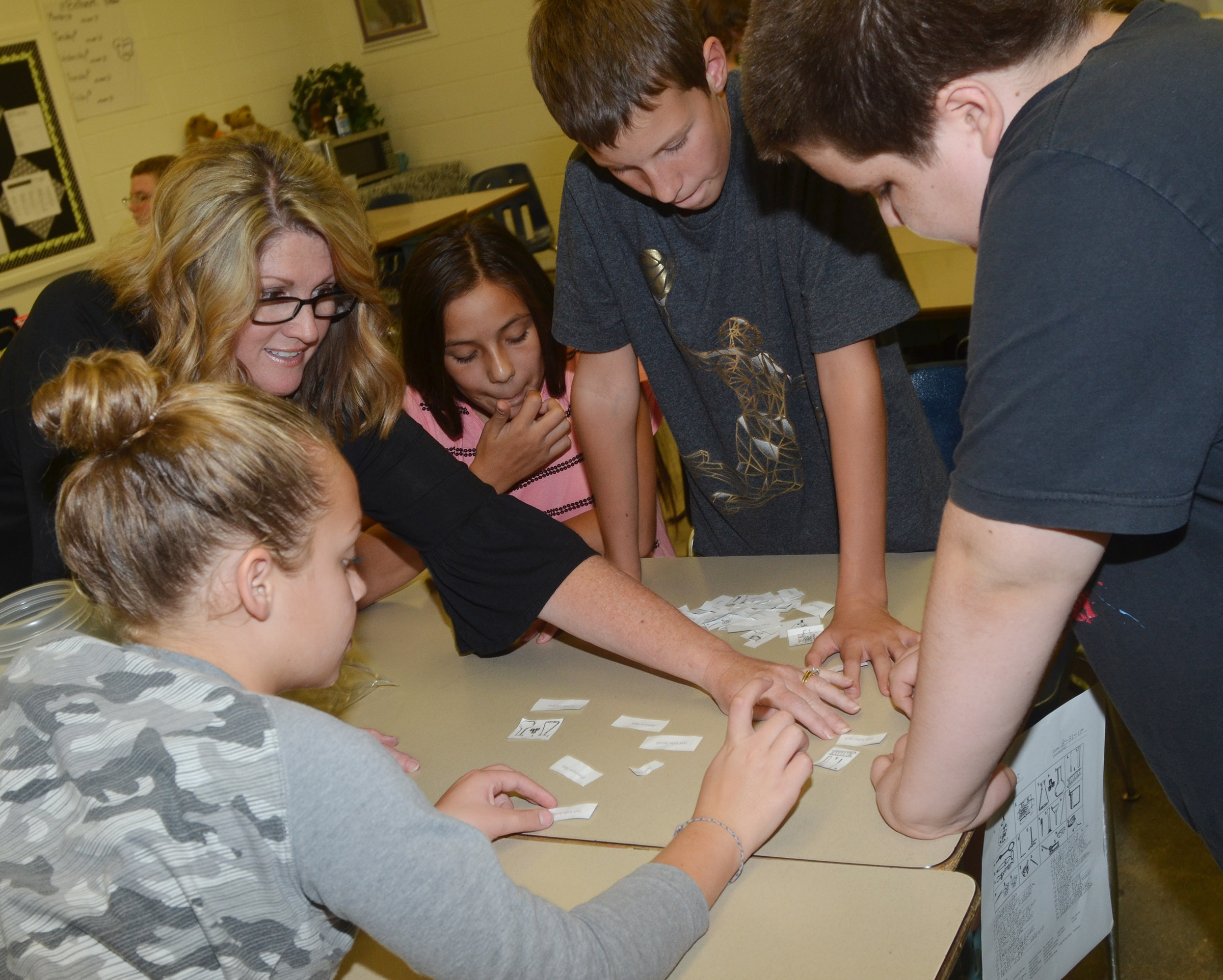 CES fifth-grade teacher Donna White checks her students' vocabulary terms to see if they are paired with the correct pictures. From left are Deanna Reardon, Marissa Segura, Rowan Petett and Joseph Gutierrez.
