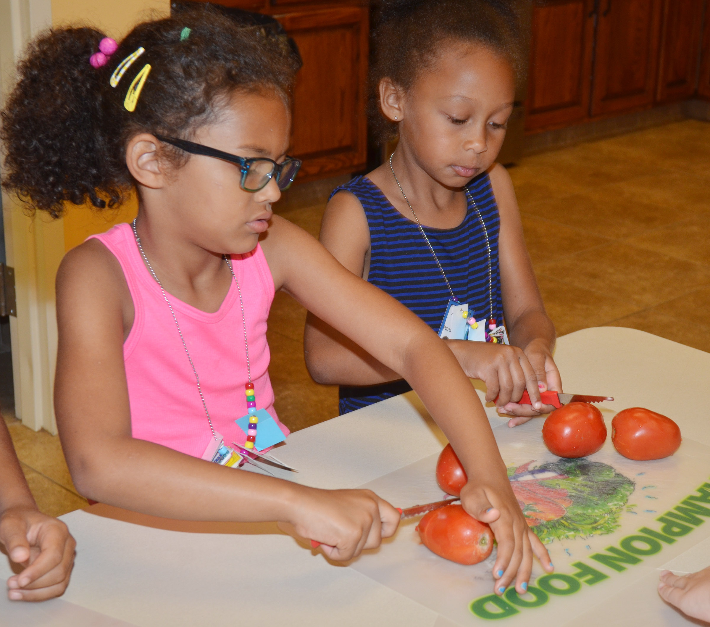 CES kindergarteners Marlee Dickens, at left, and Elyzabeth Fisher cut tomatoes as they make salsa.