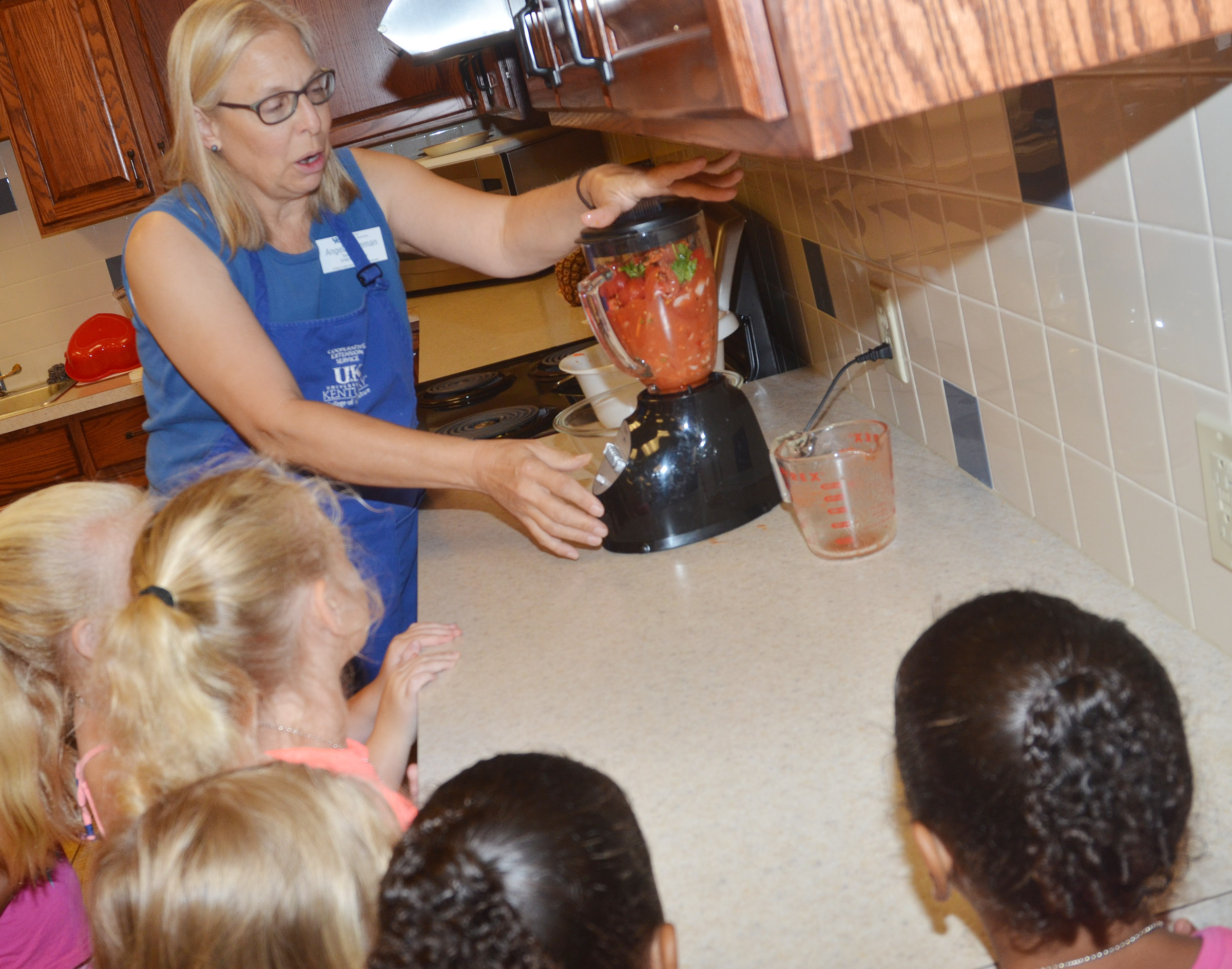 Angie Freeman, expanded foods and nutrition program assistant at Taylor County Extension Office, shows students how salsa is made in a blender.