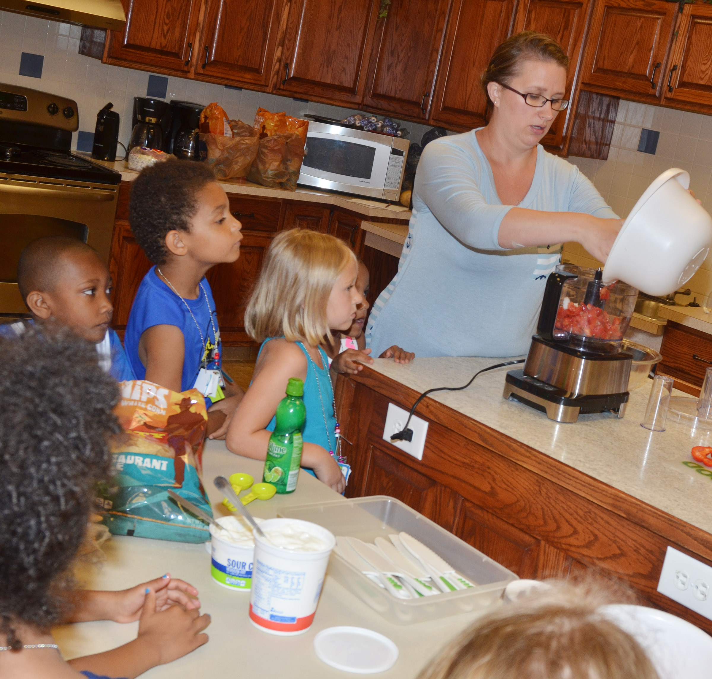 CES Wings Express assistant Jessica Williams shows how salsa is made in a food processor.