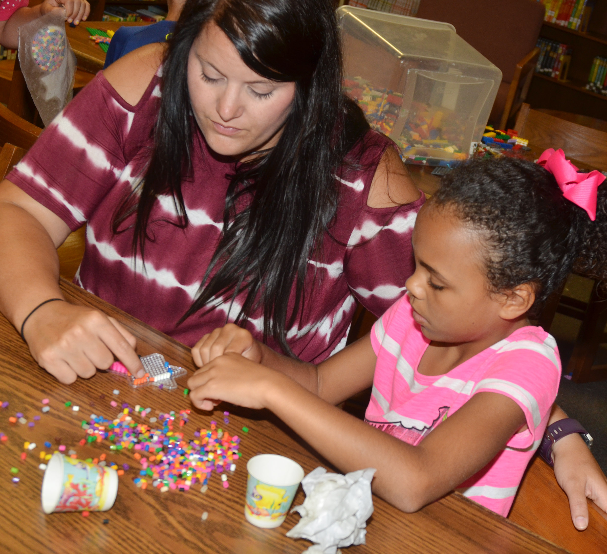 CES Wings Express assistant Miriah Cox helps second-grader Braelyn Taylor make bead art.