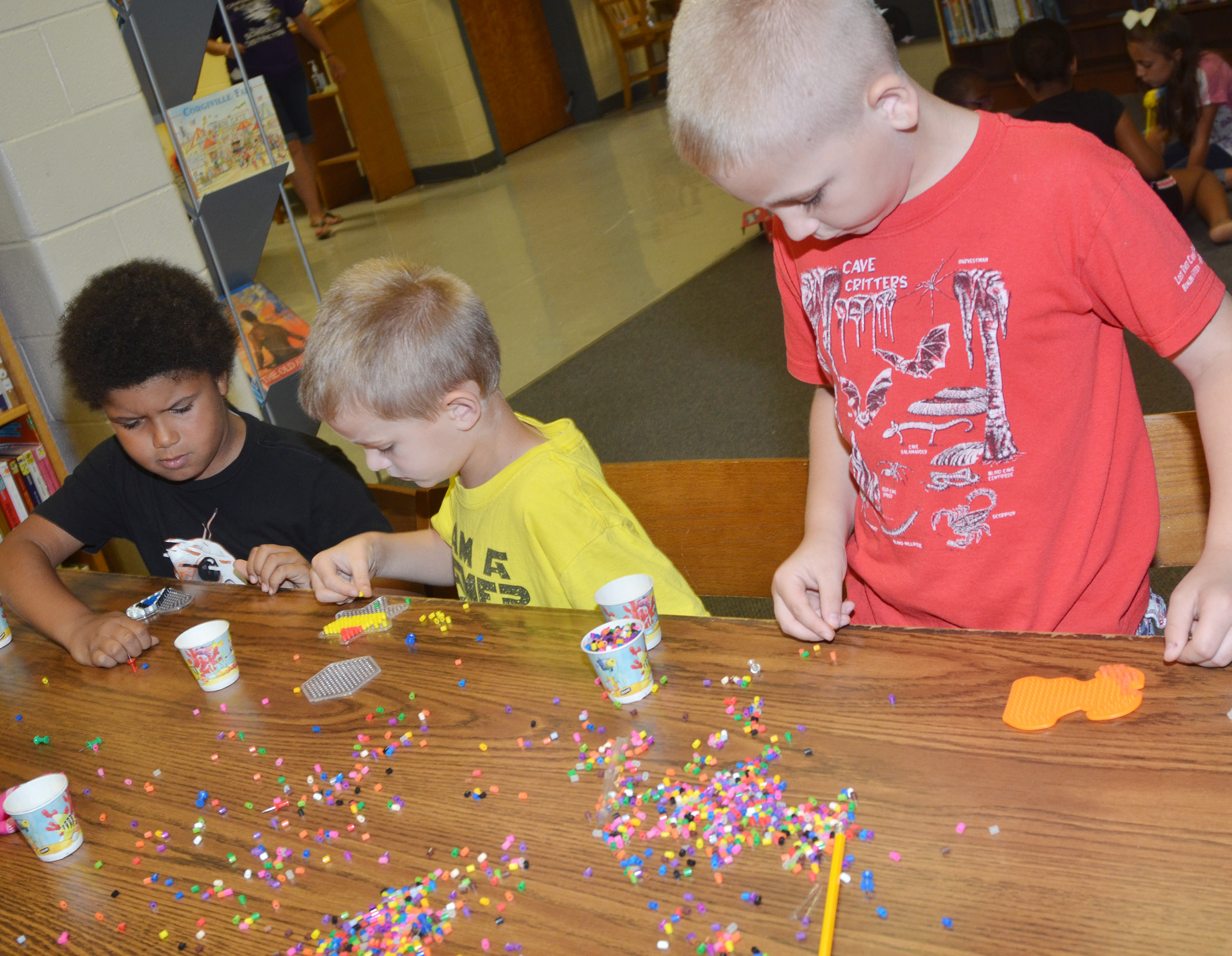 From left, CES first-graders Navon Copeland and Logan Weddle and second-grader Joseph Greer make bead art.