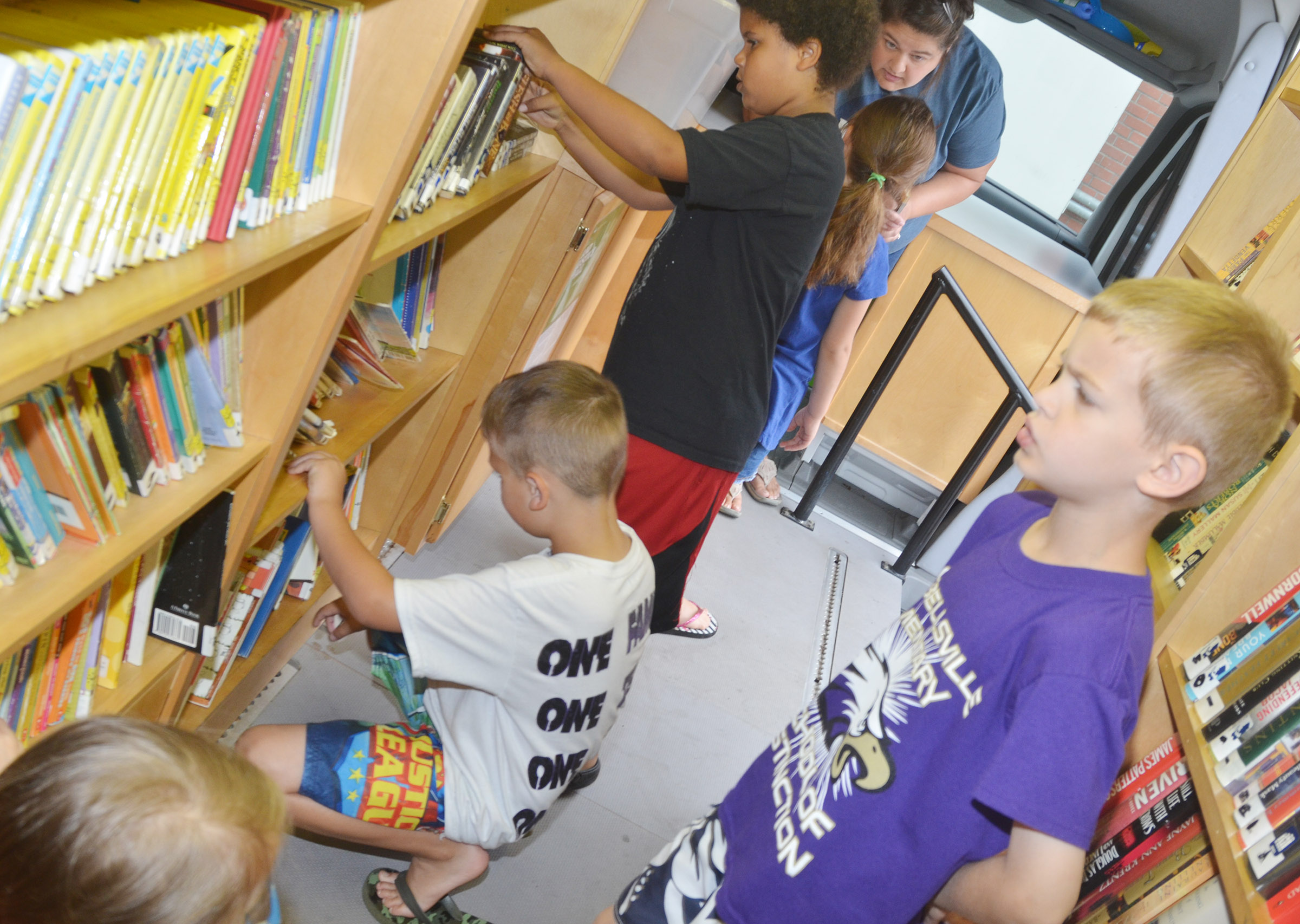 CES first-grader Logan Weddle and his classmates search for books on the bookmobile.