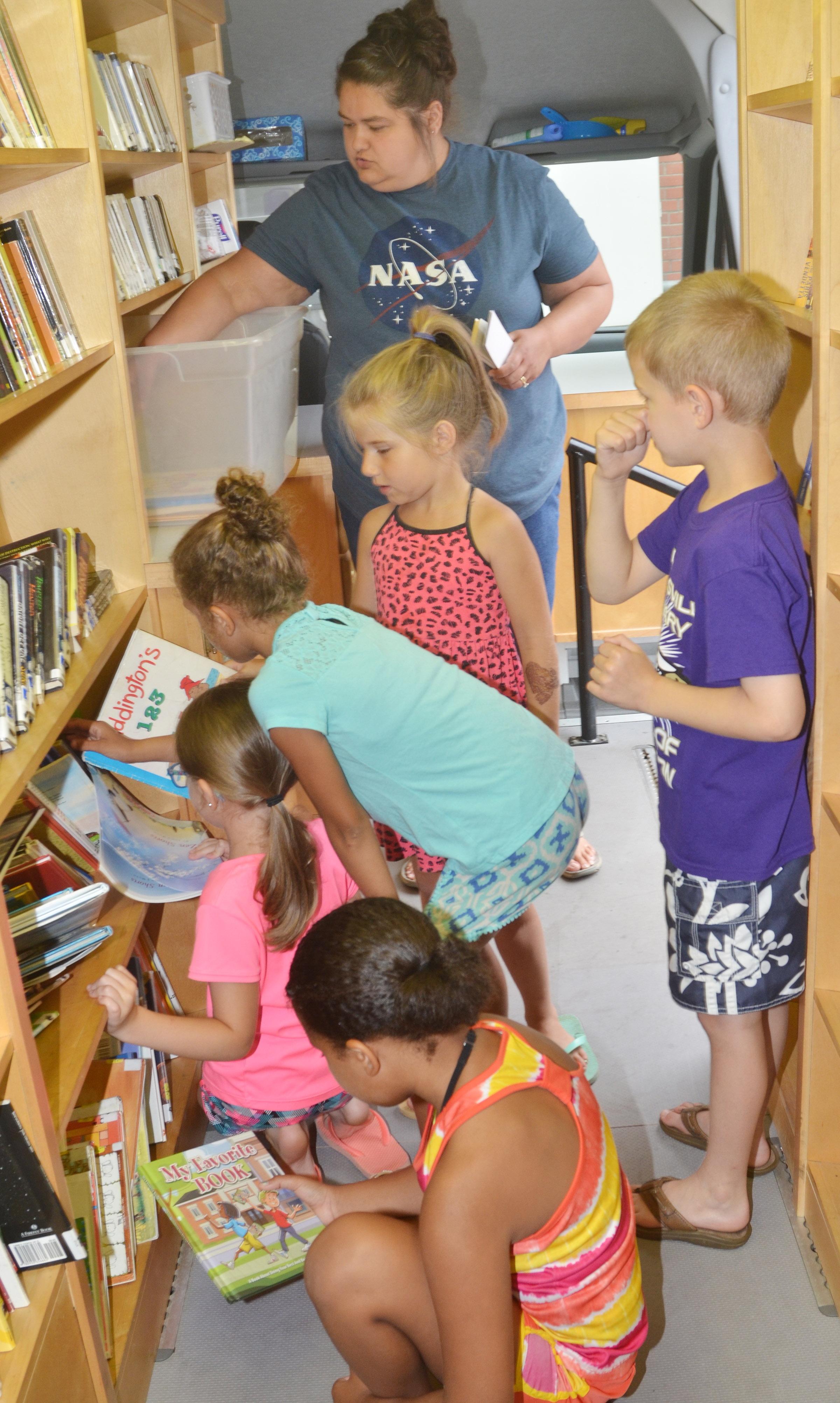 CES Wings Express students search for books on the bookmobile with Sarah Hampton, Taylor County Public Library outreach librarian.