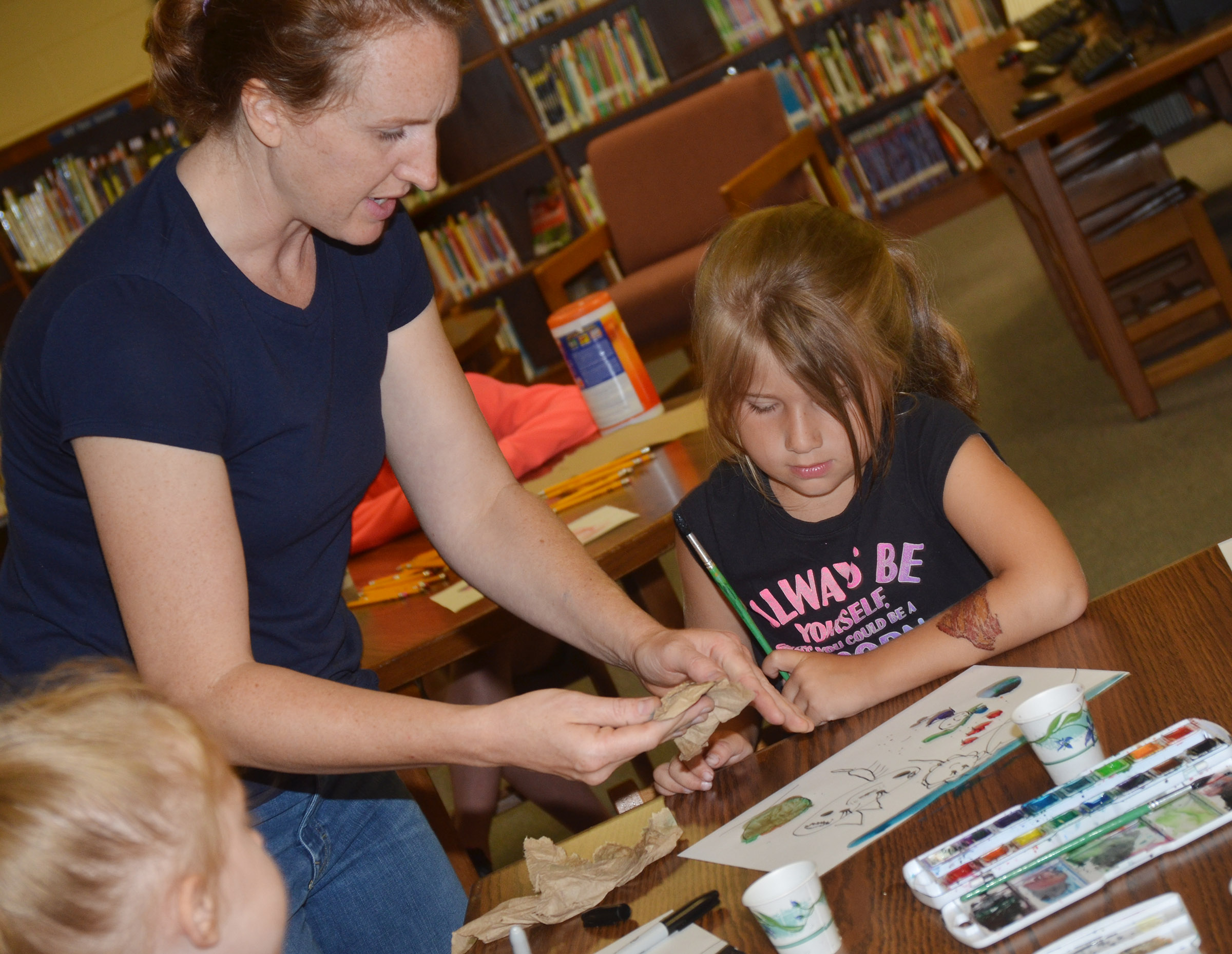 Heather Russell of Method Studio helps first-grader Kenady Hayes paint.