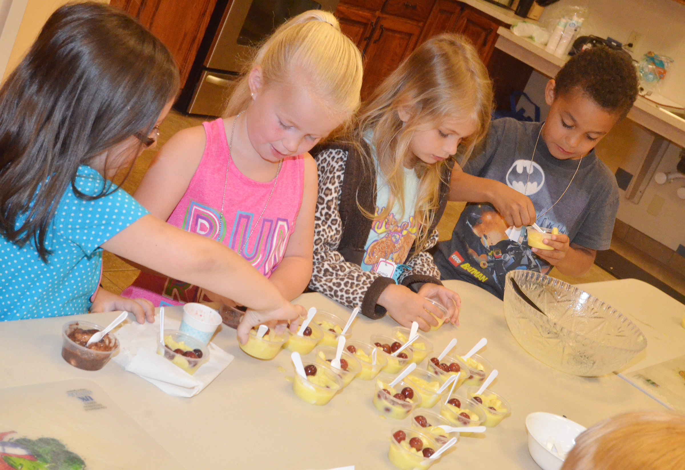 From left, CES kindergarteners Trinity Clark, Lillie Judd, Gracie Gebler and Quincy Travis sample a healthy yogurt snack.