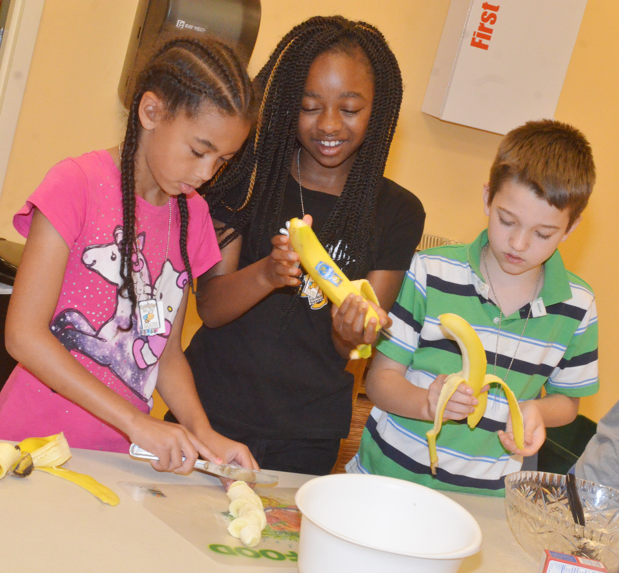 From left, CES third-graders De'Asia Fisher, Tiffani Gaddie and Landon Tucker prepare bananas as they make a healthy snack.