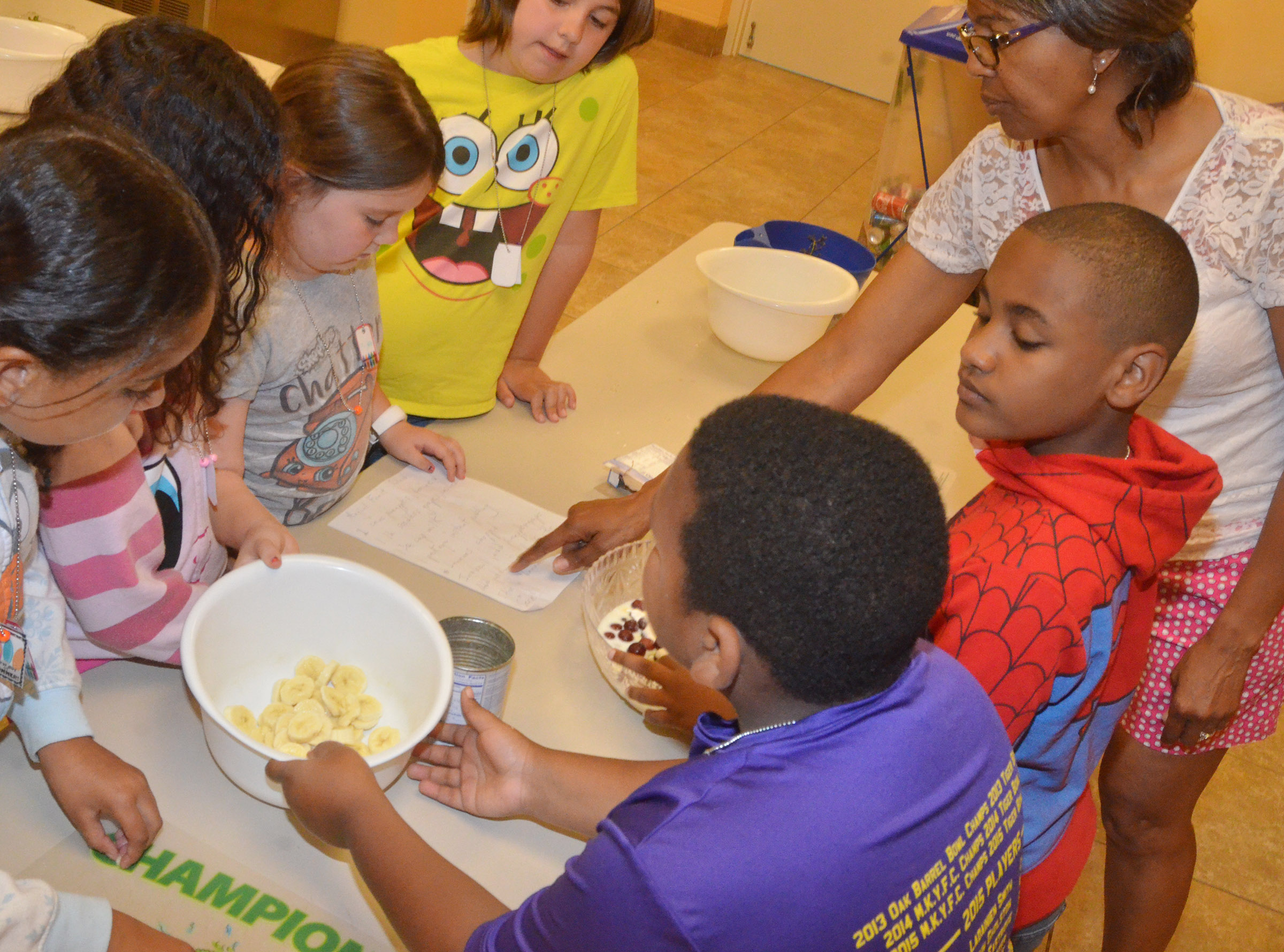 CES teacher Doretha Sanders helps third-graders as they prepare to make a healthy yogurt snack.