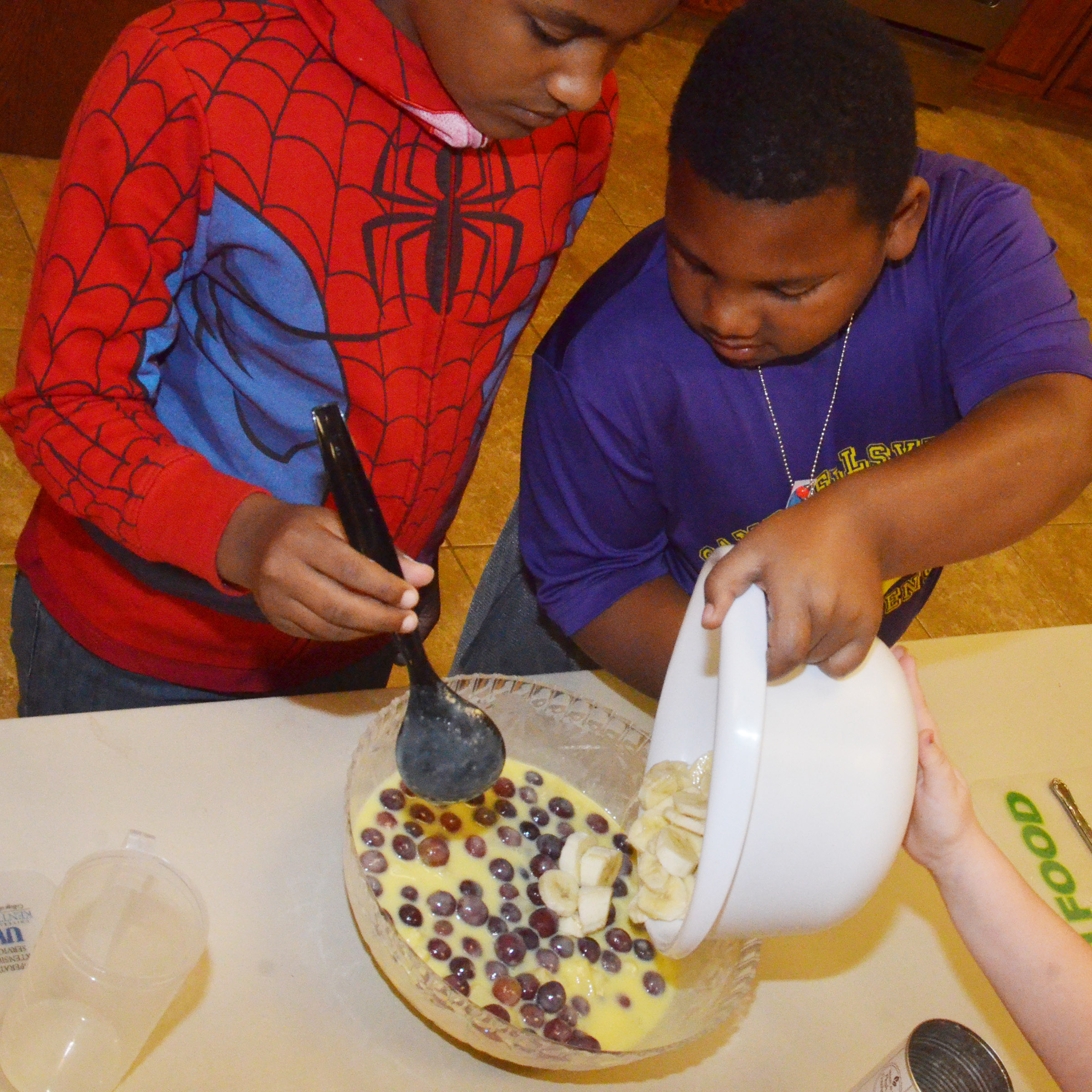 CES third-graders Shaiden Calhoun, at left, and Malikiah Spurling stir their yogurt snack.