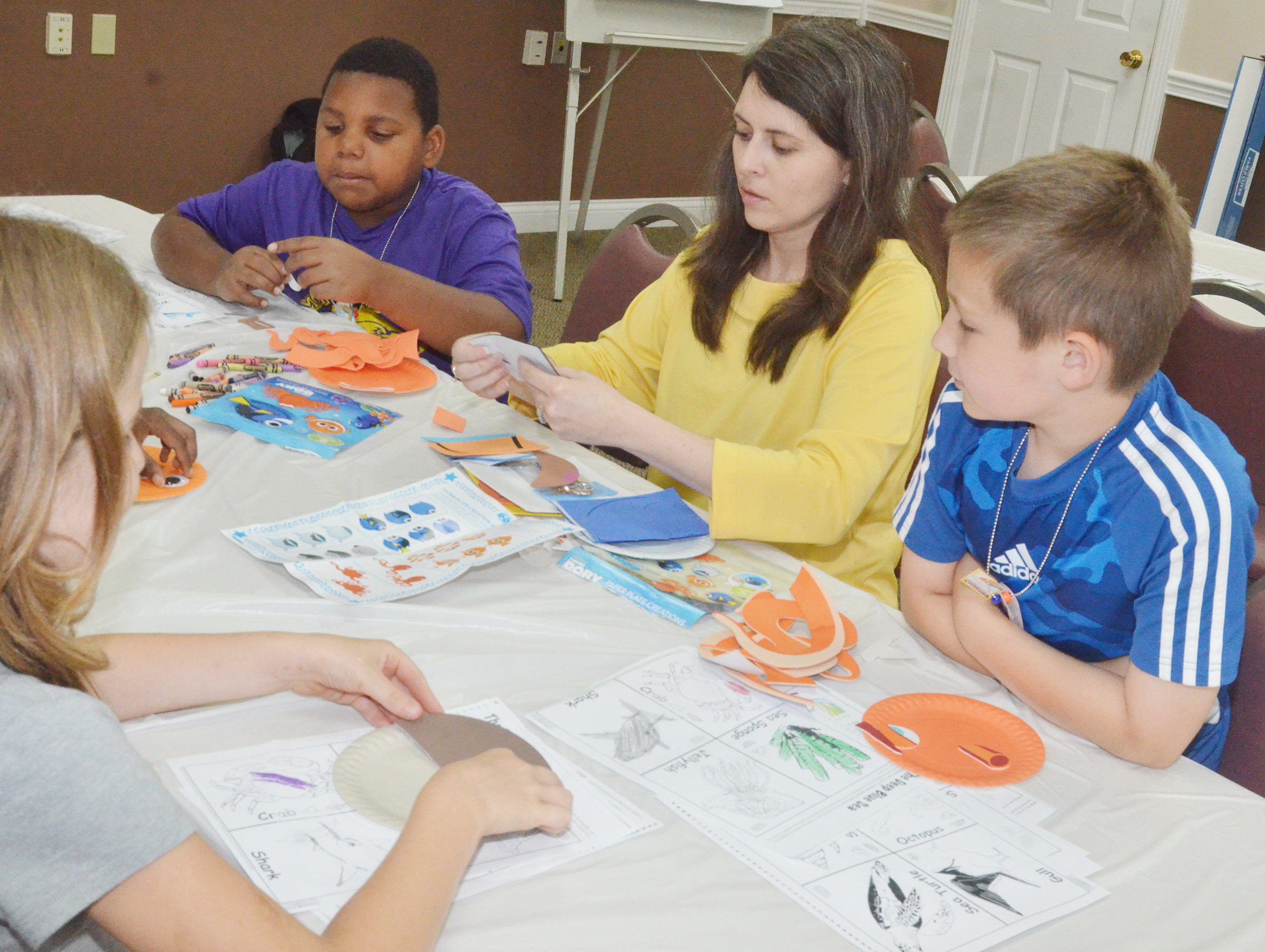 Amanda Sublett, extension agent for 4-H youth development at Taylor County Extension Office, helps CES Wings Express students make ocean animals out of paper plates. At left is third-grader Malikiah Spurling and at right is third-grader Grayson Dooley.