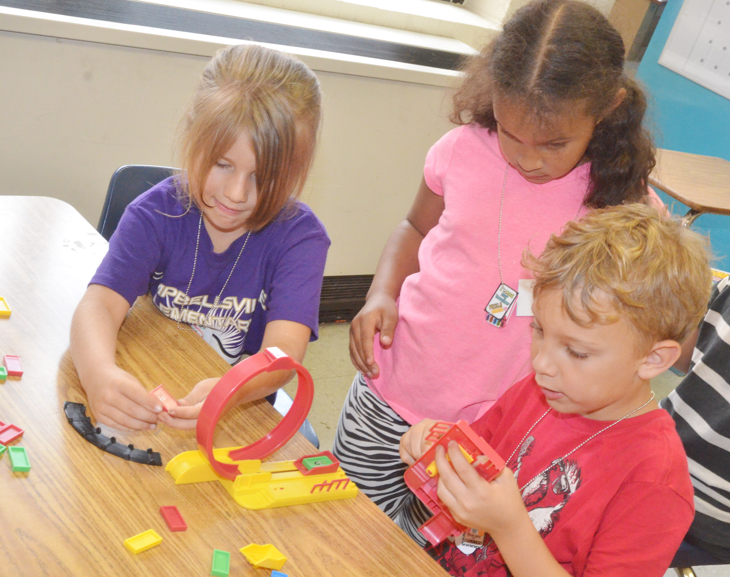 CES first-graders, from left, Kenady Hayes, Amani Bridgewater and Gabe Prior build a racetrack.