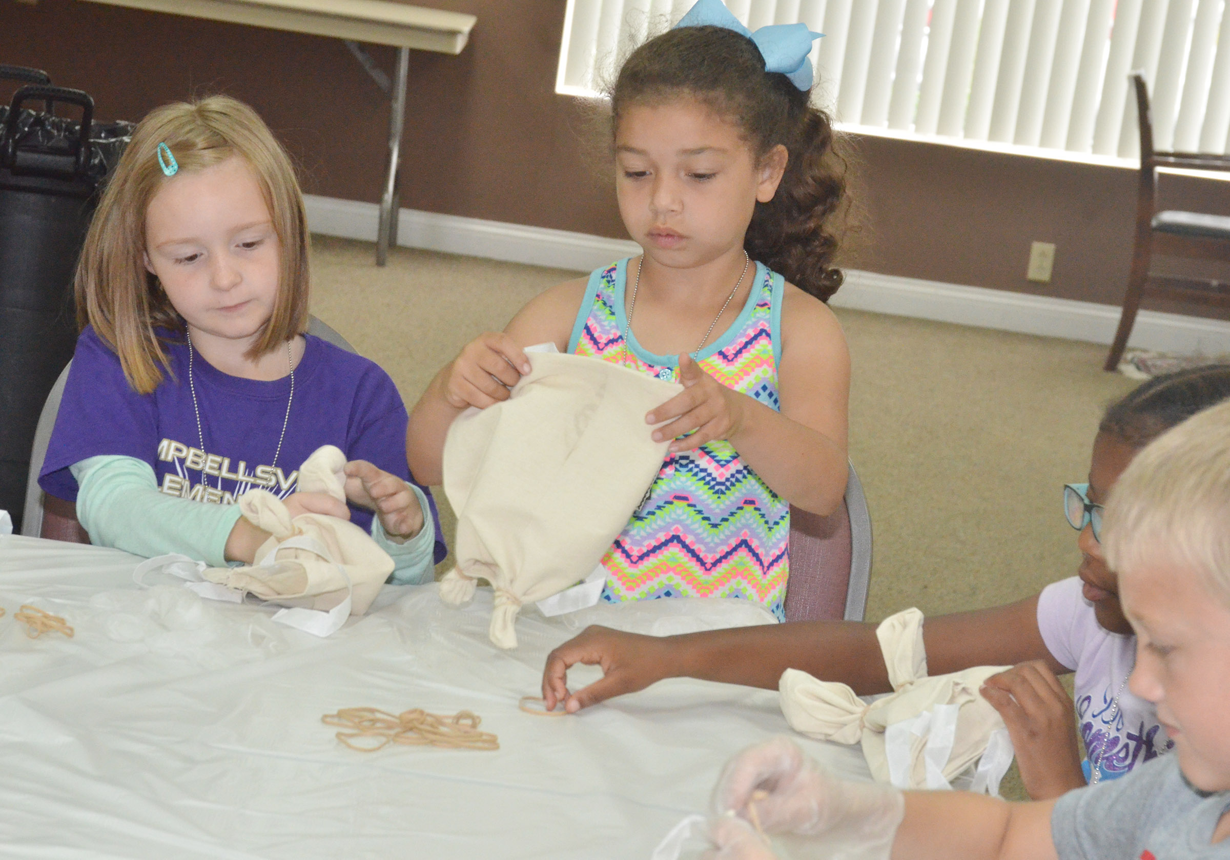 CES first-graders Gracie Murphy, at left, and Ammarissa Nunez tie knots in their bags so they can tie-dye them.