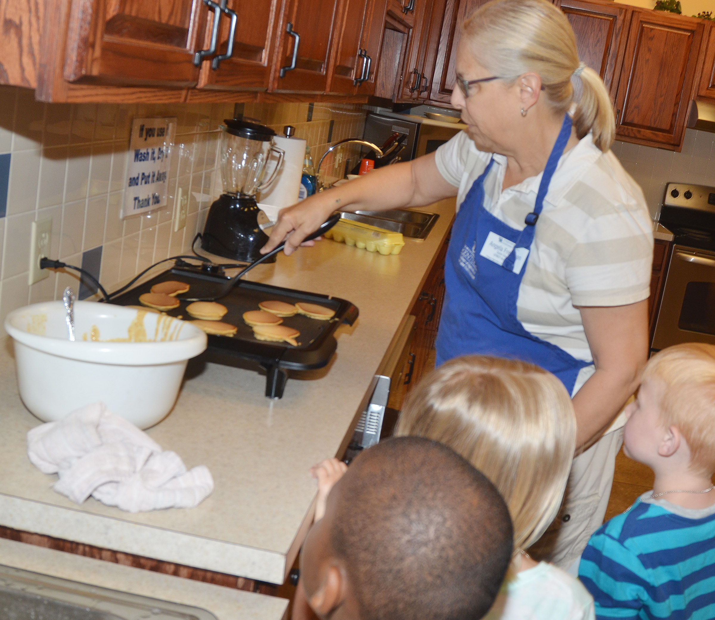 Angie Freeman, expanded foods and nutrition program assistant at Taylor County Extension Office, shows CES kindergarteners how to make pancakes.