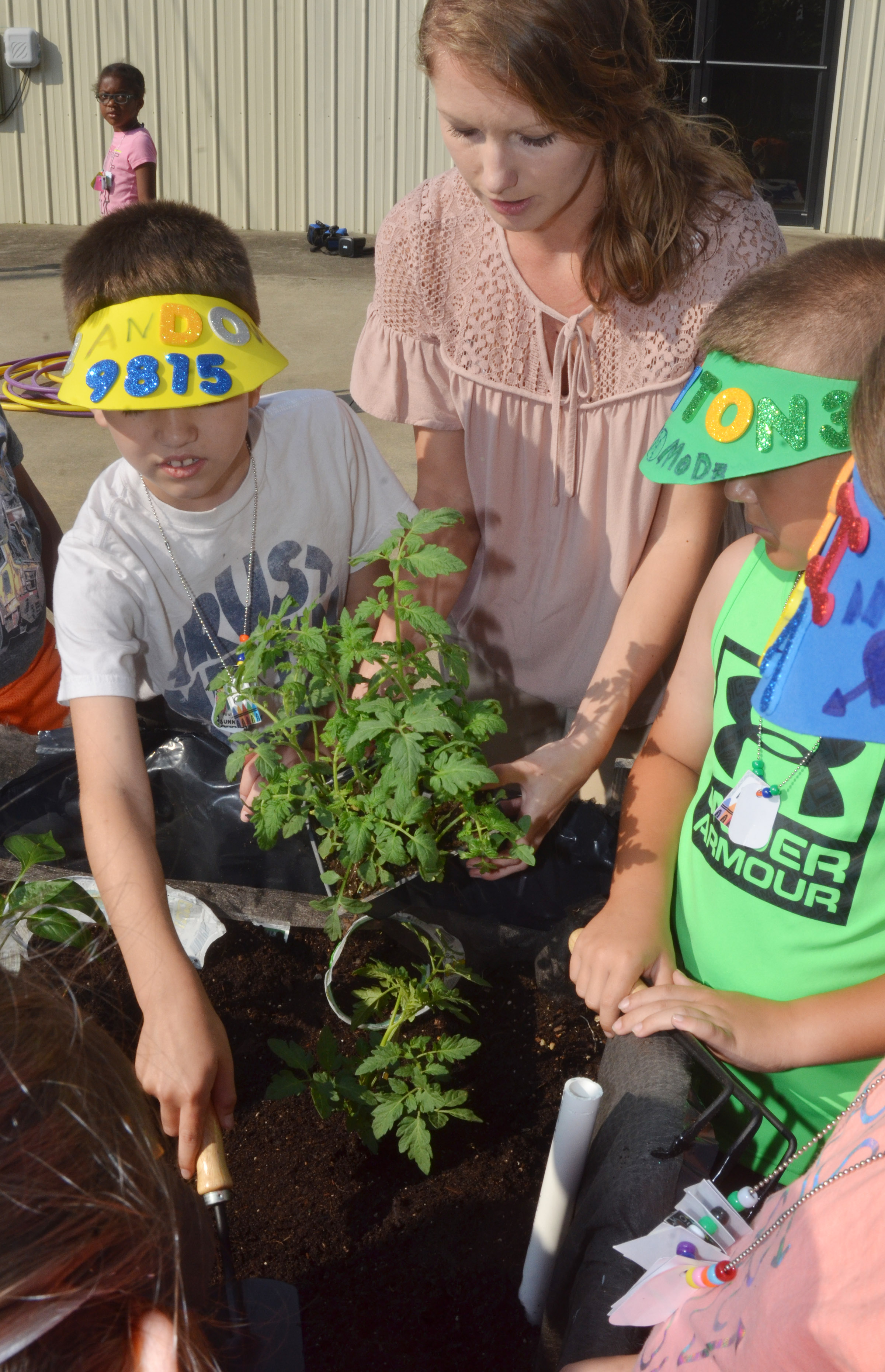 Kara Back, extension agent for horticulture at Taylor County Extension Office, helps CES third-grader Landon Tucker, at left, and second-grader Cayton Lawhorn plant flowers.