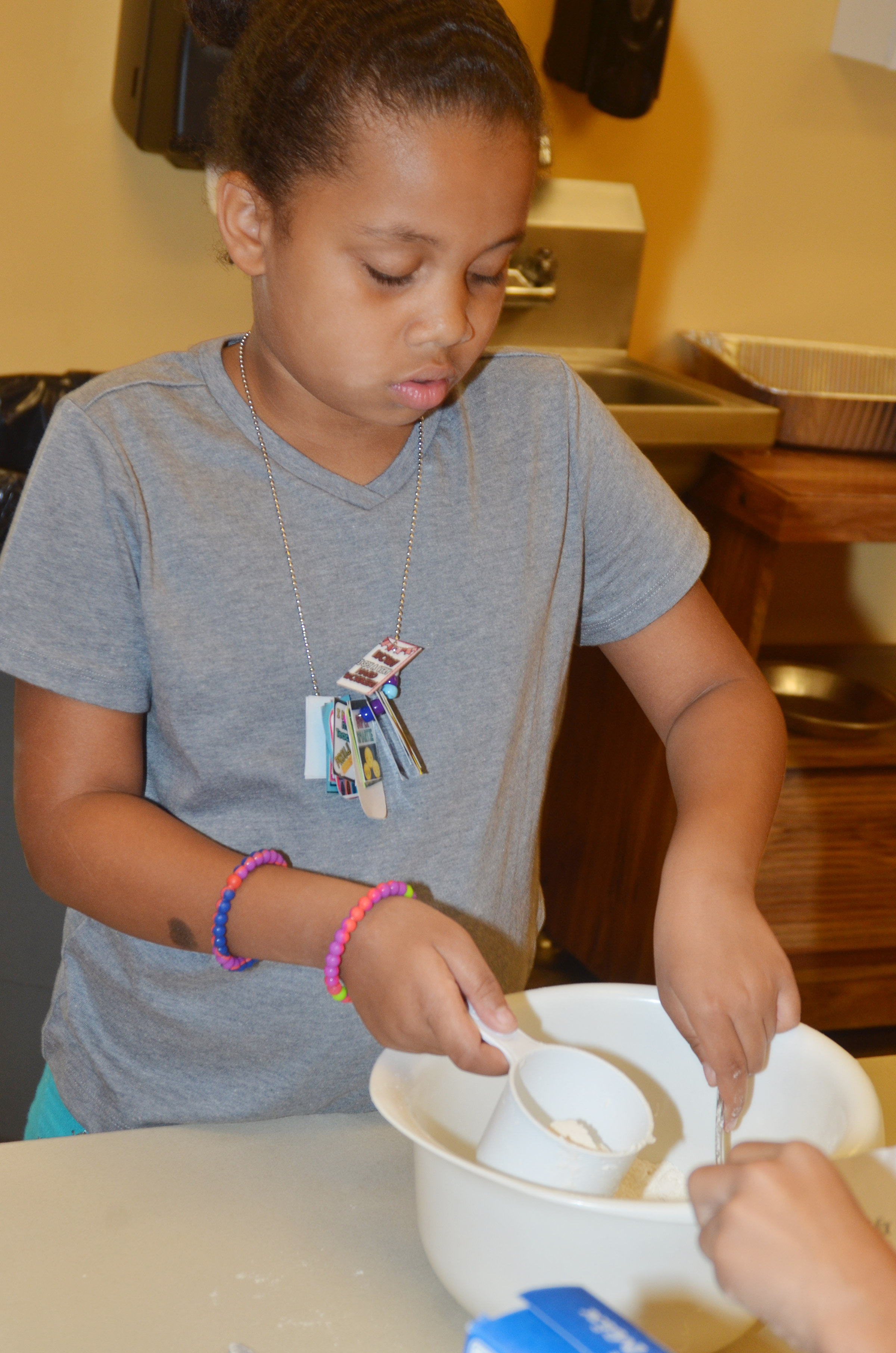 CES first-grader Journey Webb measures ingredients to make pancakes.