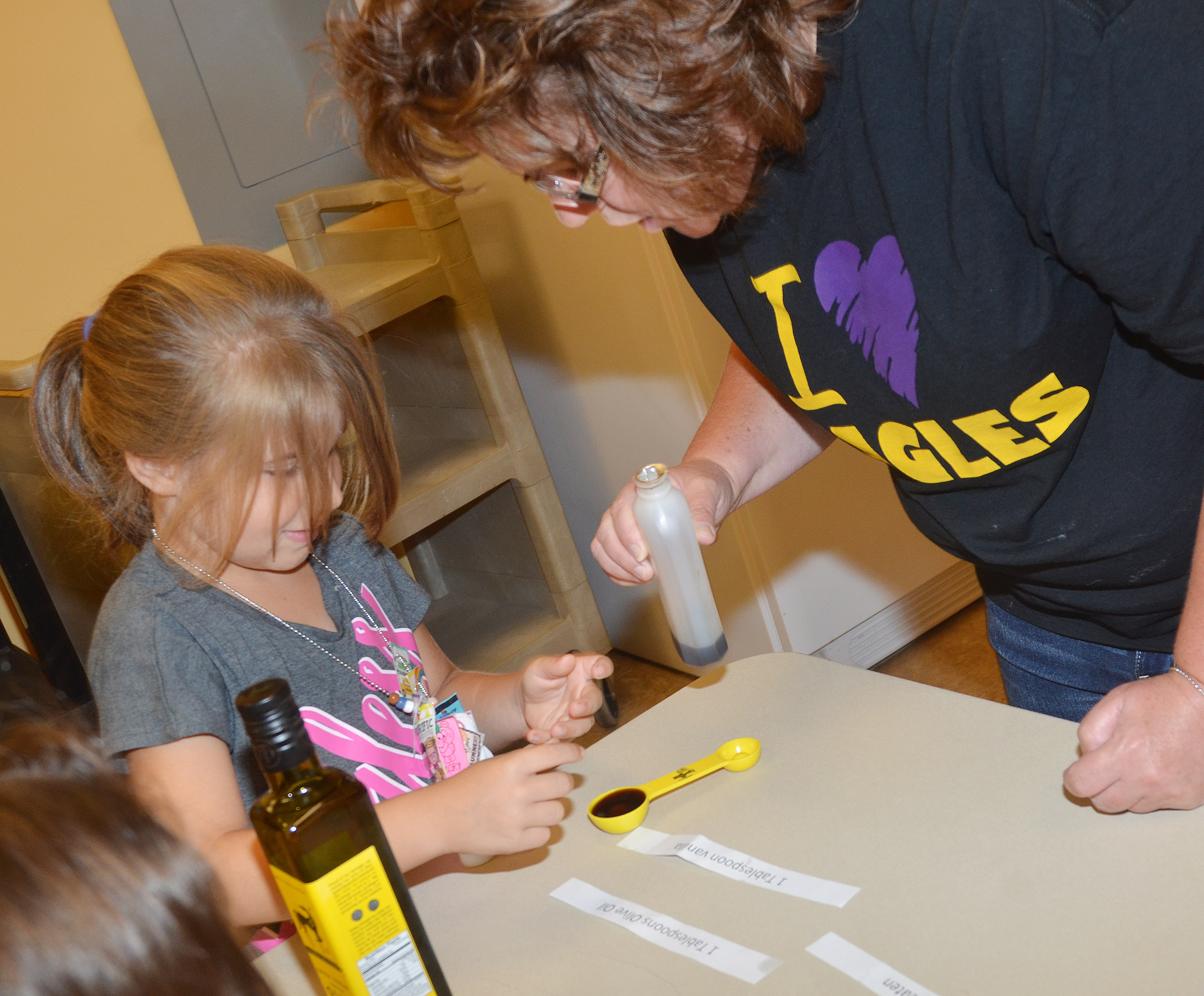 CES Wings Express assistant Tracey Rinehart helps first-grader Kenady Hayes measure vanilla.
