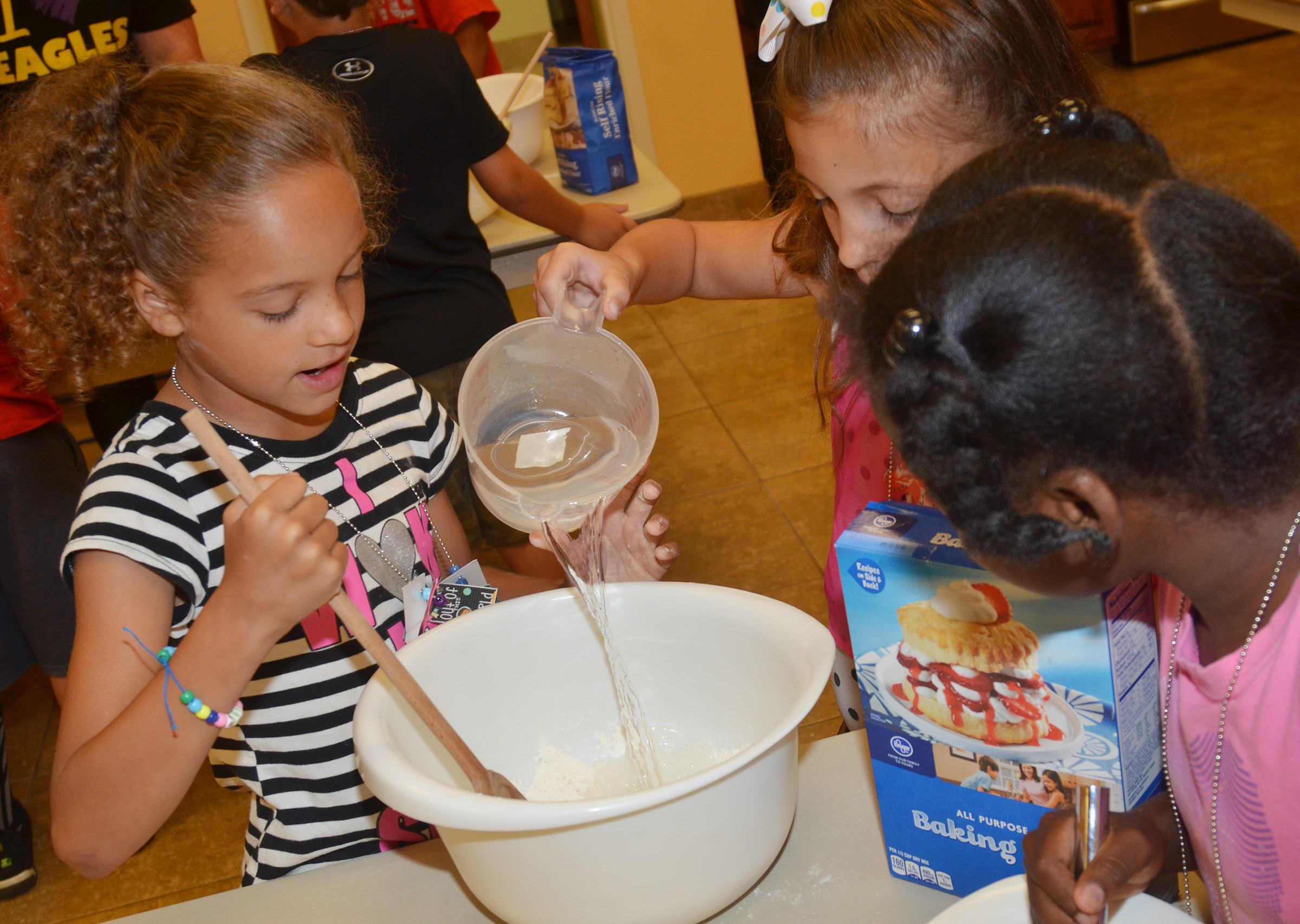 CES first-grader Keiava Thompson stirs as classmate Lillian Martin adds water to their pancake mixture and first-grader Destini Gholston watches.