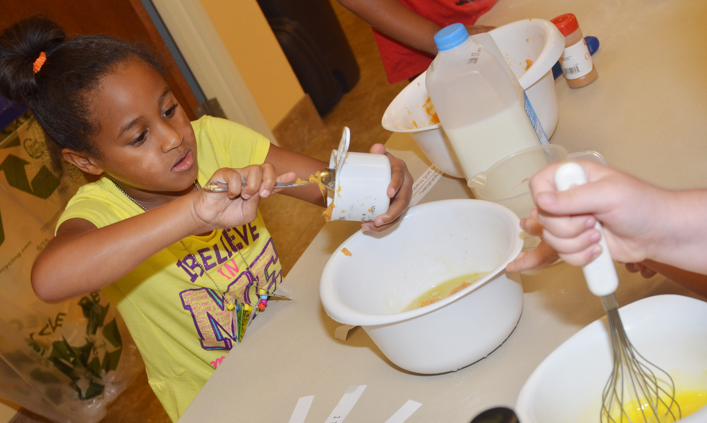 CES first-grader Kadance Ford adds ingredients to her pancake mixture.