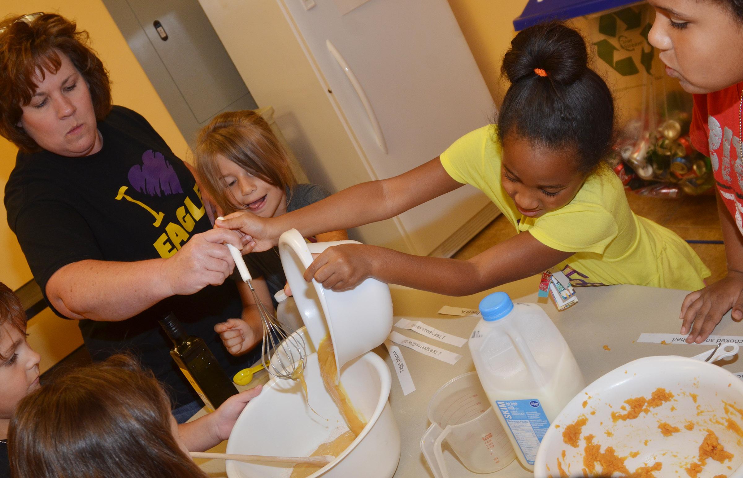 CES Wings Express assistant Tracey Rinehart helps first-graders add ingredients to their pancake mixture.
