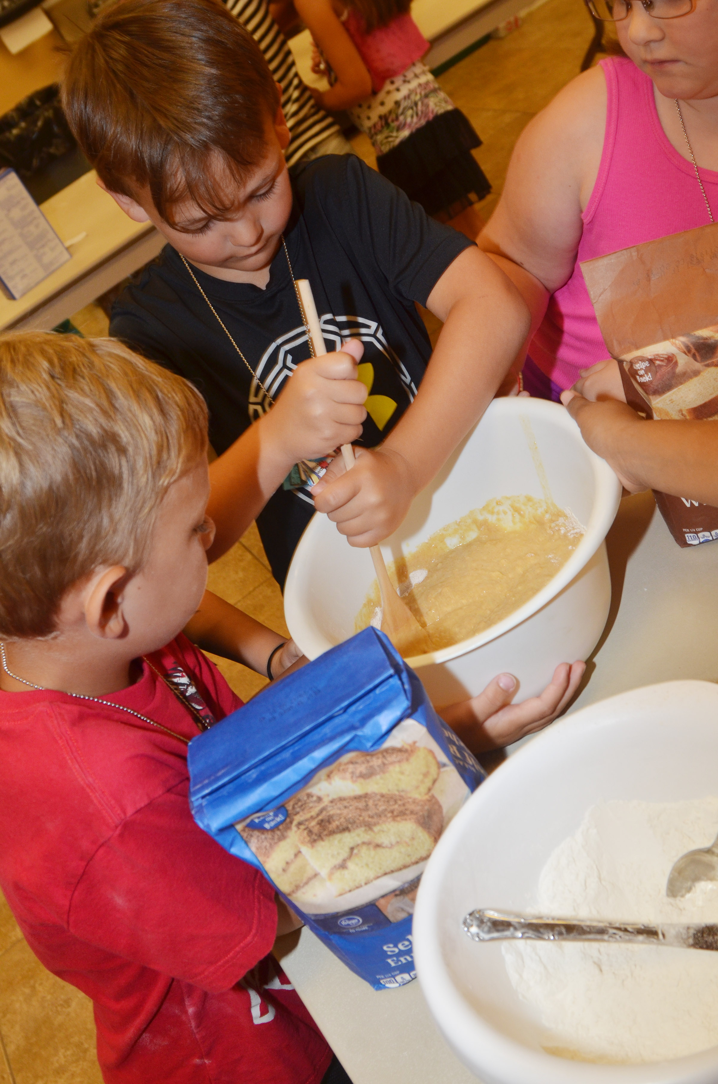 CES first-grader Brendan Martin stirs his group's pancake mixture.