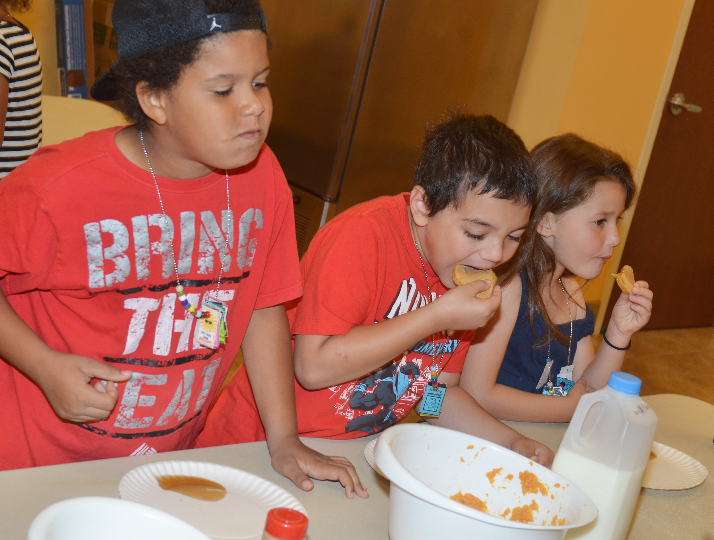 From left, CES first-graders Navon Copeland, Diego Aquino and Stella Newcomb sample the pancakes they made.
