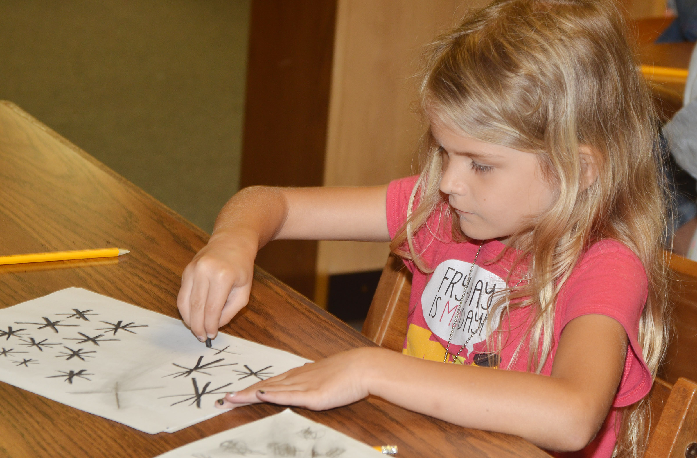 CES kindergartener Gracie Gebler draws with charcoal.