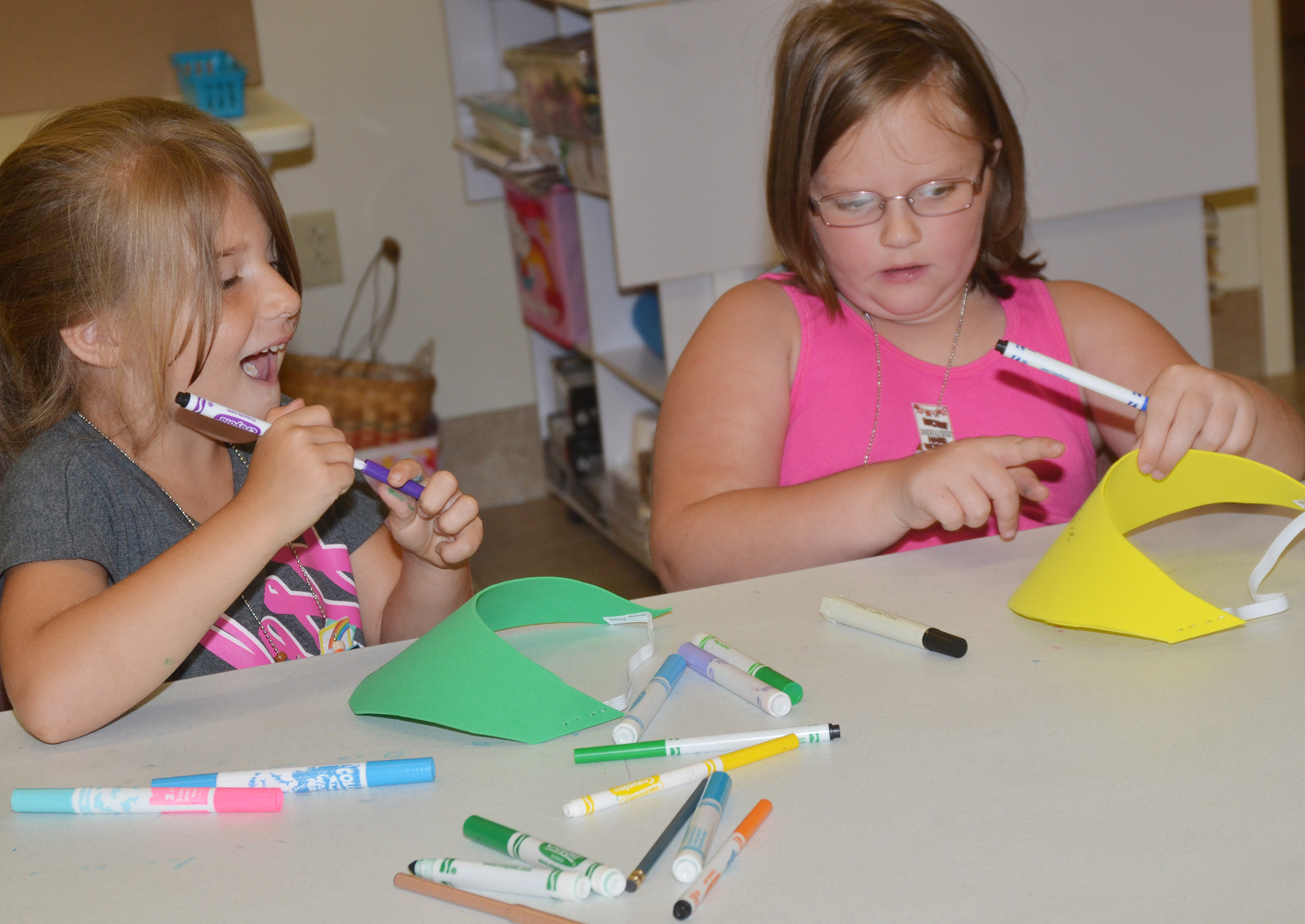 CES first-graders Kenady Hayes, at left, and Justice Albrecht decorate hats together.
