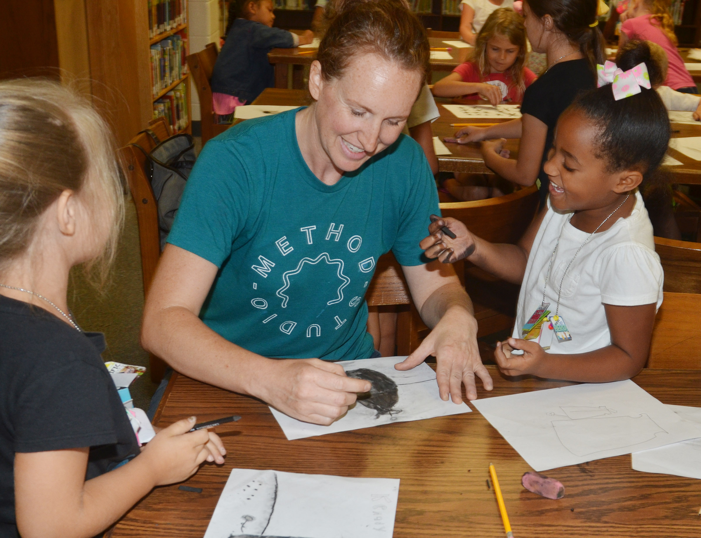 Heather Russell of Method Studio helps first-graders Kenady Hayes, at left, and Kadance Ford draw with charcoal.