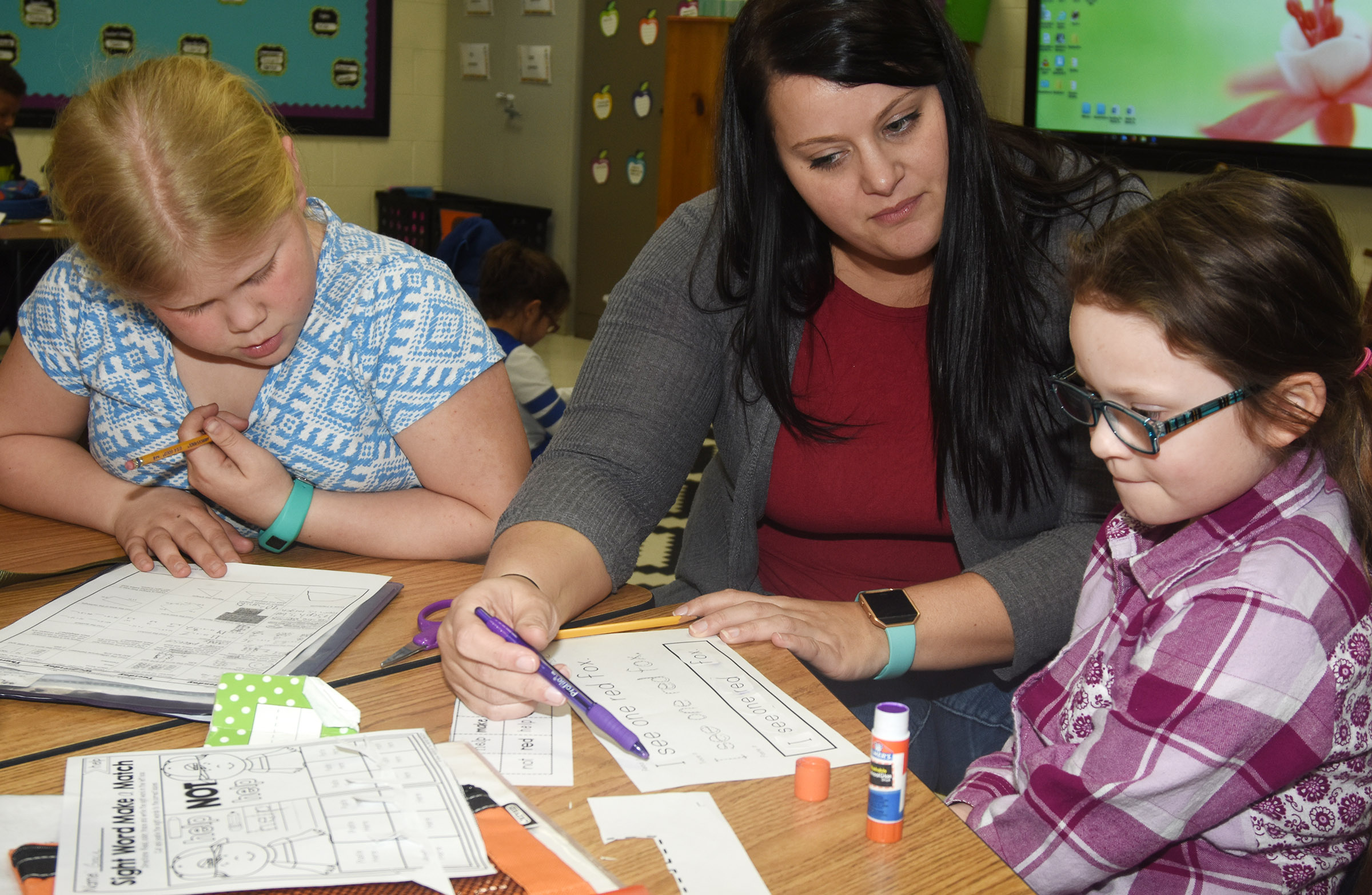 CES first-grade teacher Miriah Cox works with third-grader Lily Coots, at left, and Gracie McKenzie as they complete their homework during a Wings Express session.
