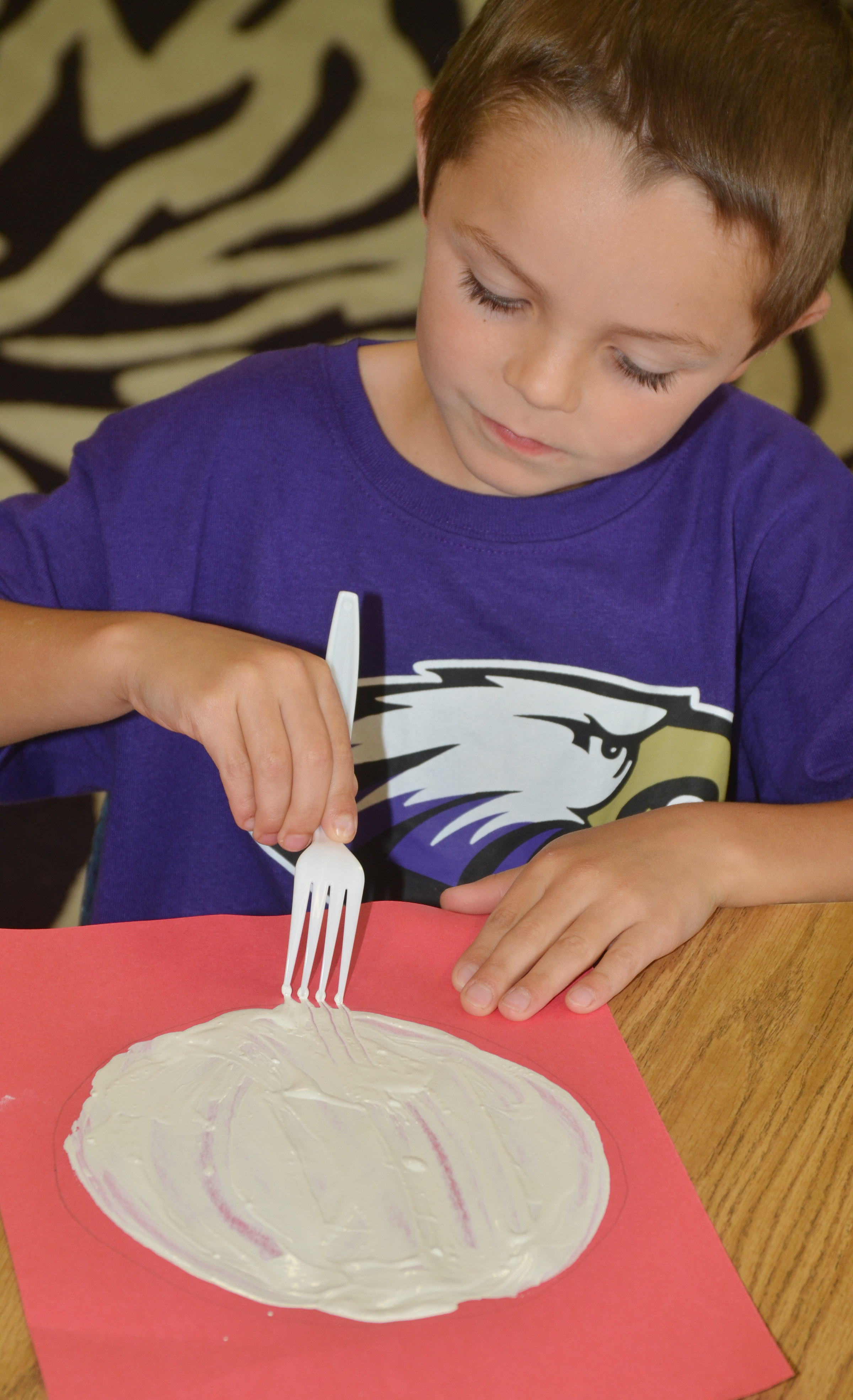 CES kindergartener Hayden Goff paints with a fork to make his panda's face.