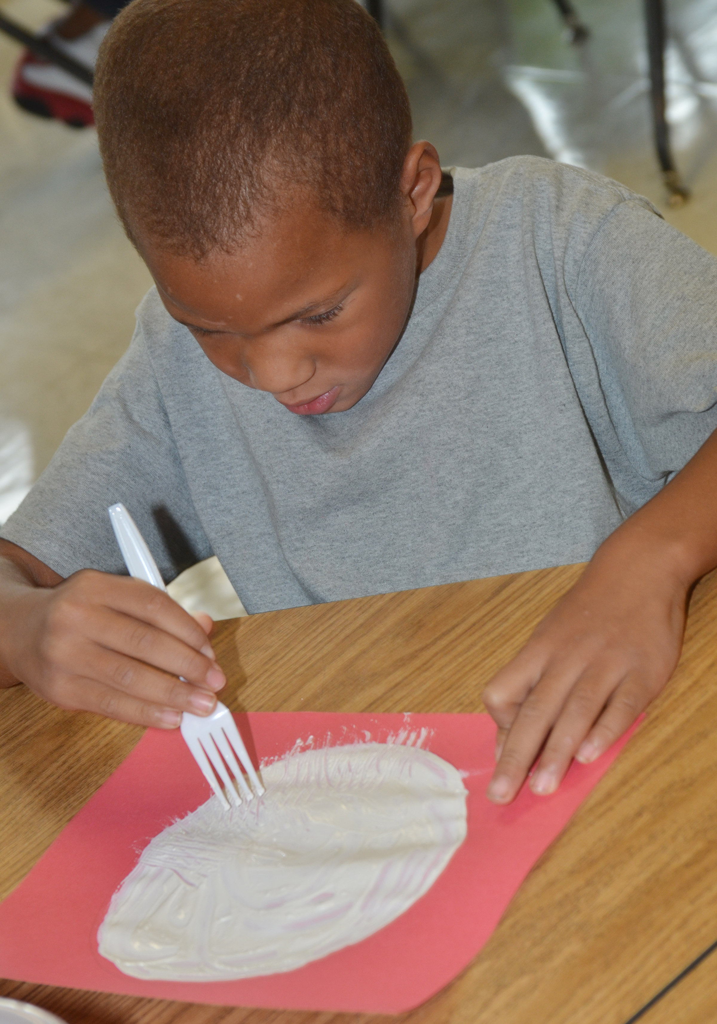 CES kindergartener Jamerius Miller paints with a fork to make his panda's face.